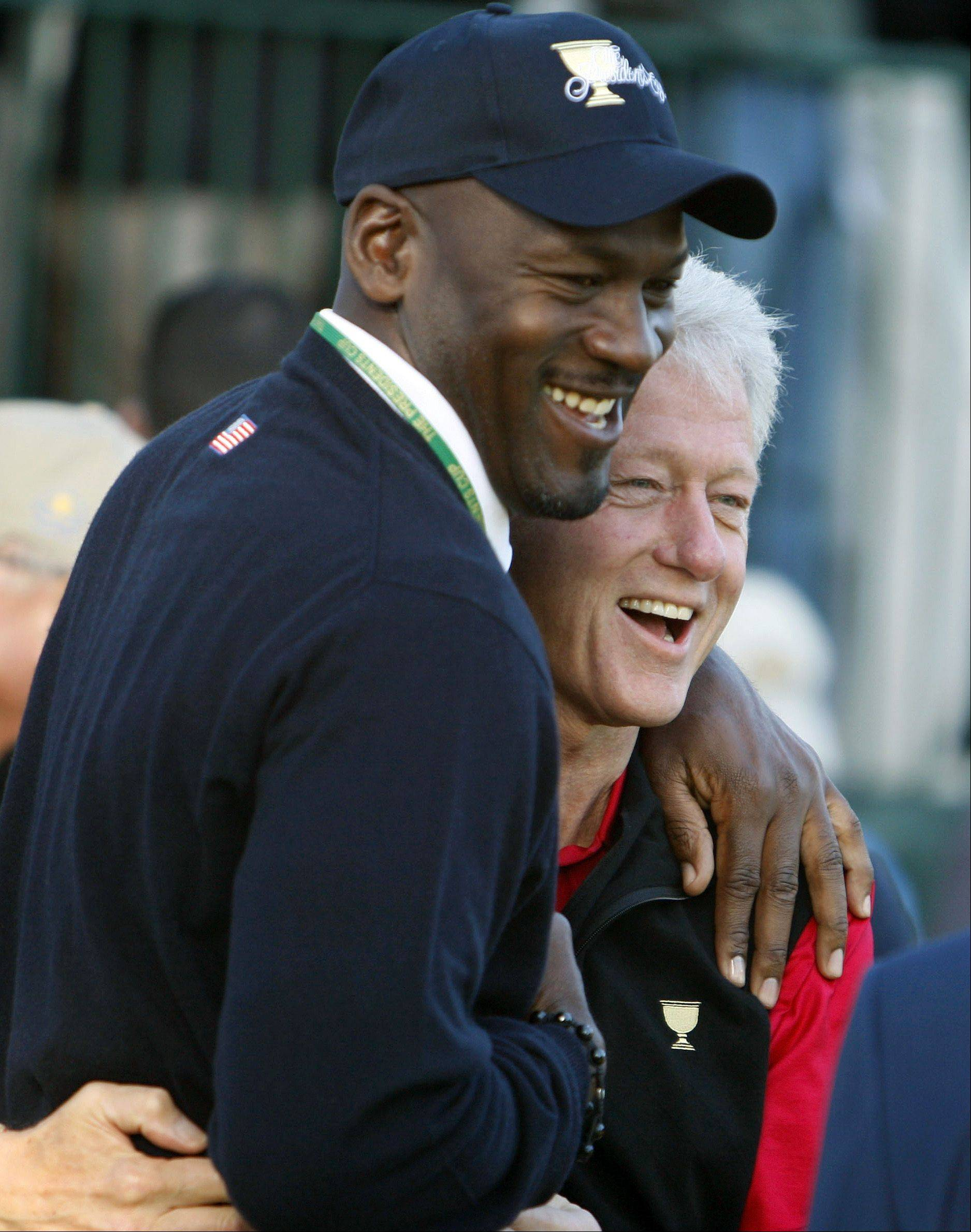 Former United States President Bill Clinton, right, jokes with basketball great Michael Jordan during a team photo session for the Presidents Cup golf competition Tuesday, Oct. 6, 2009, in San Francisco. Jordan is on hand as a guest of U.S. captain Fred Couples.