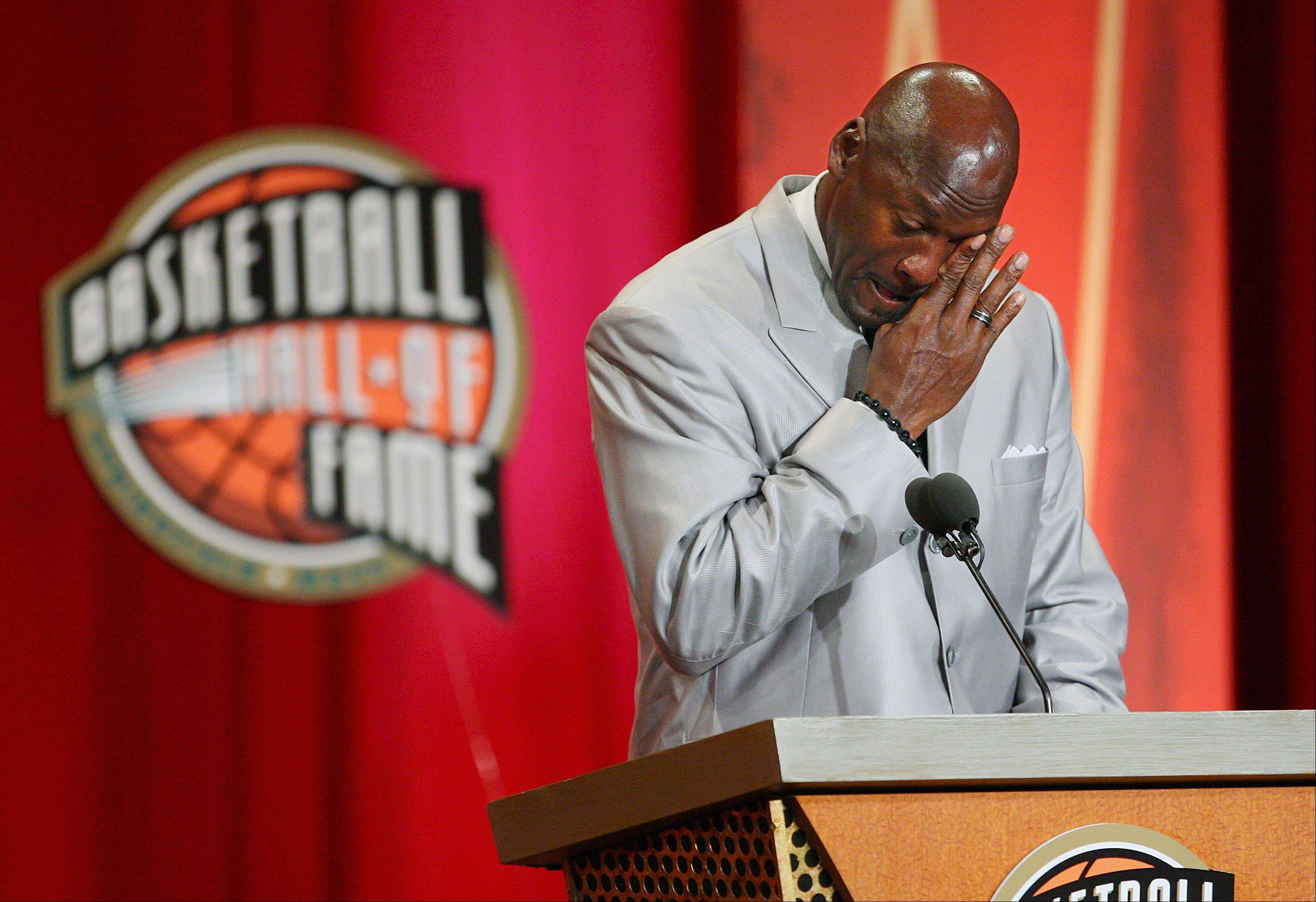 Former Chicago Bulls and Washington Wizards guard Michael Jordan wipes tears from his eyes as he prepares to deliver his address during his enshrinement ceremony into the Naismith Basketball Hall of Fame in Springfield, Mass., Friday, Sept. 11, 2009.