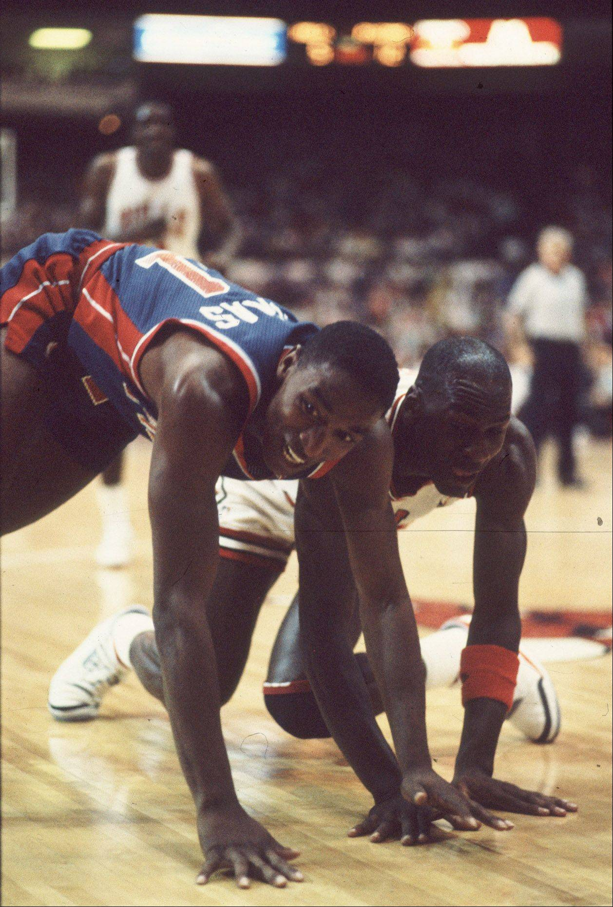 Michael Jordan and Detroit's Isiah Thomas hit the floor after scrambling for a ball.