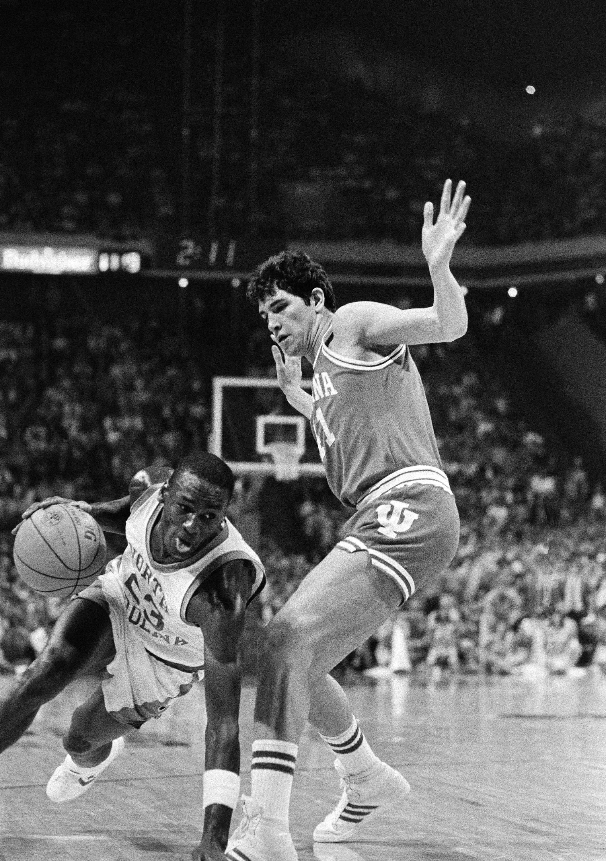 North Carolina forward Michael Jordan sticks out a hand and his tongue Thursday March 23, 1984 trying to drive past Indiana forward Mike Giomi on March 23, 1984 at Atlanta Omni. Indiana won the NCAA East Regional semifinal game, 72-68, and will meet Virginia Saturday.