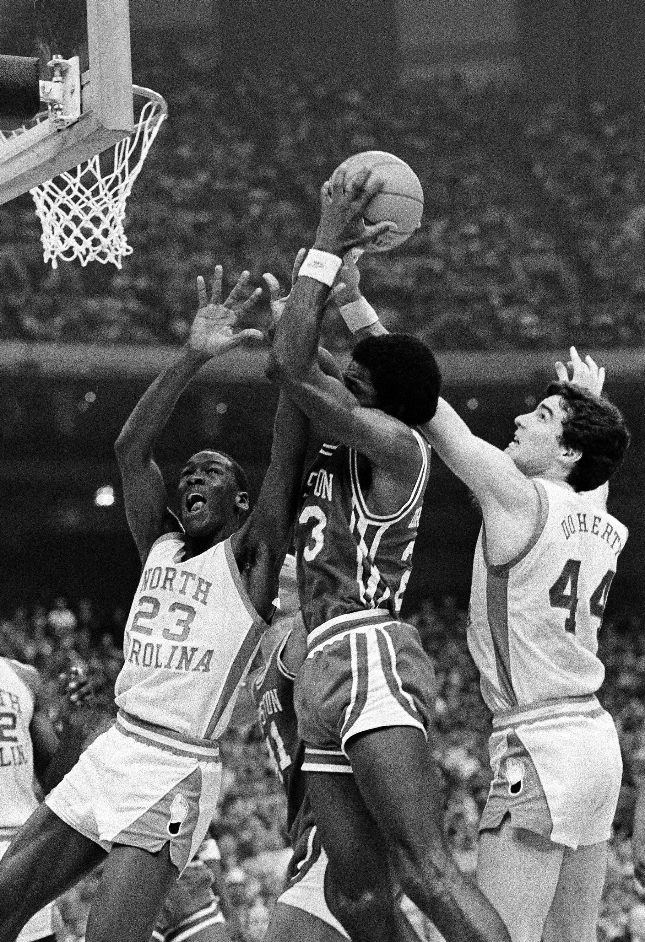 University of Houston's Clyde Drexler, center, grabs the rebound as University of North Carolina players Michael Jordan (23) and Matt Doherty (44) get in the action during NCAA semi-final play in New Orleans, March 28, 1982. North Carolina won, 68-63 and will meet Georgetown University in final action Monday night.