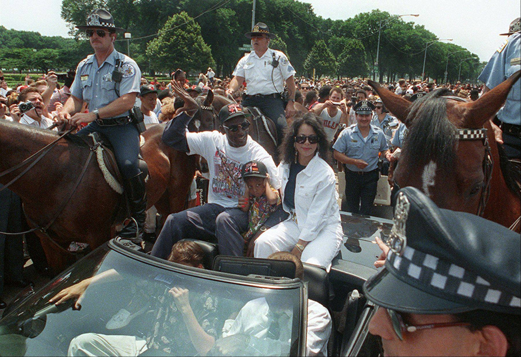 Michael Jordan rides in their first victory parade to Grant Park with his son and wife Juanita in the Chicago.