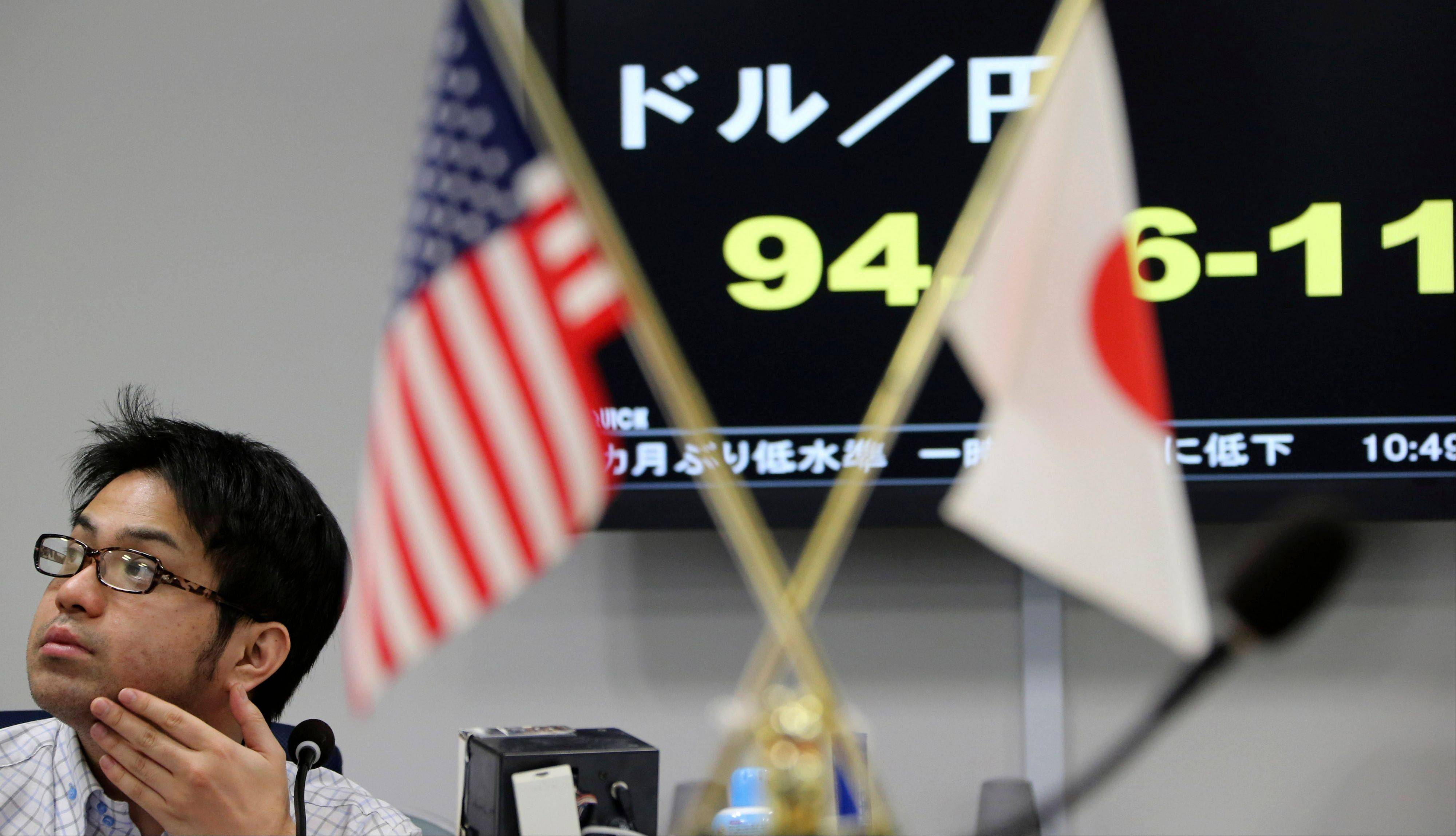 $PHOTOCREDIT_ON$$PHOTOCREDIT_OFF$ A foreign exchange broker works in front of a screen displaying the current dollar to yen rate as an American and Japanese, flag are displayed at the office in Tokyo, Monday