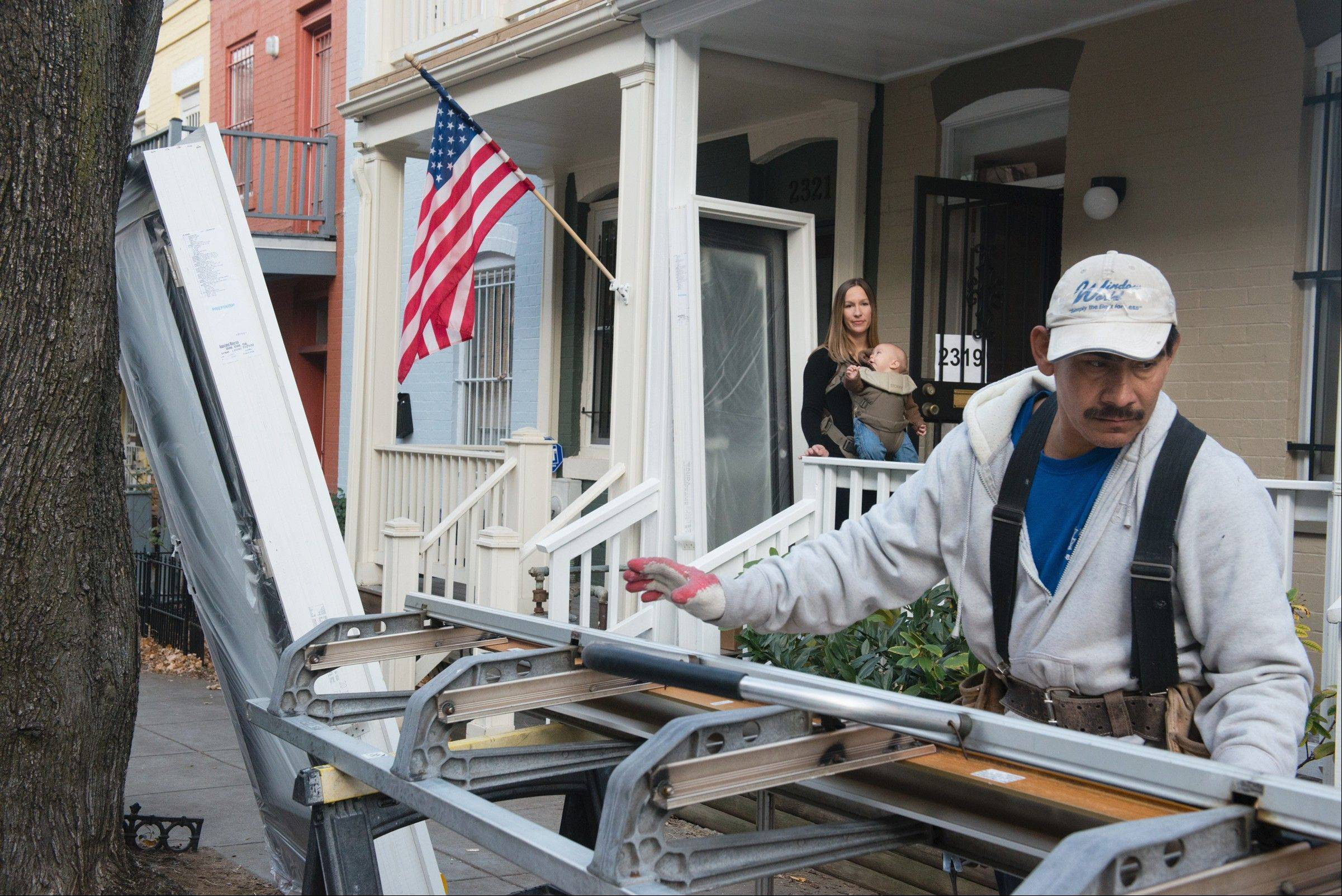 Miguel Orallana of Window World installs a door as homeowner Blakeslee Crumbliss, with her 6-month-old son Owen, look on. She is preparing her Washington, D.C. house for rental.
