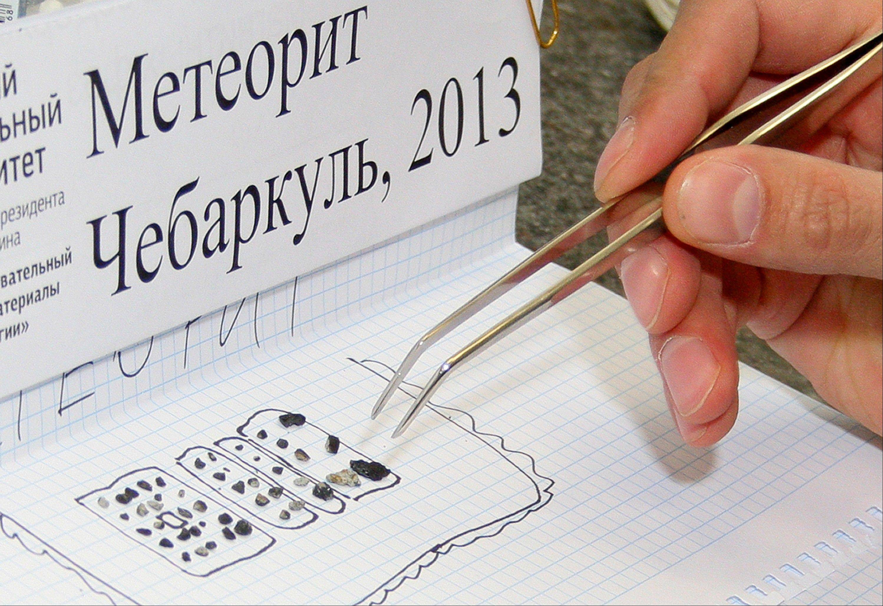 ASSOCIATED PRESS A researcher examines pieces of a meteorite in a laboratory in Yekaterinburg on Monday. Researchers have determined that the small stone-like pieces found near Lake Cherbarkul in the Chelyabinsk region are pieces of the meteorite that exploded over the region Feb. 15.