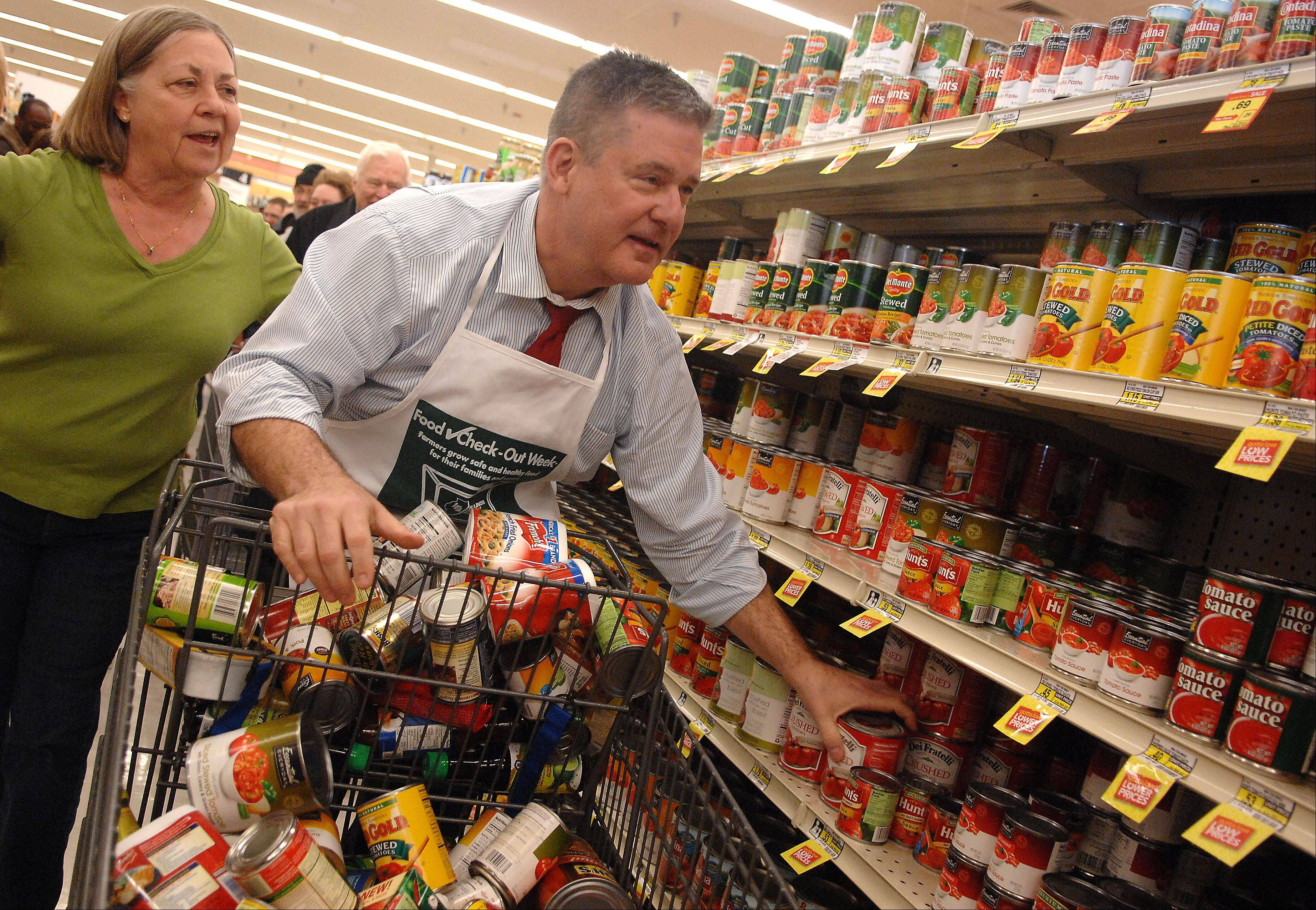 State Treasurer Dan Rutherford gets help from Linda Dahms of the Batavia Interfaith Food Pantry while competing in the Food Check-Out Challenge Monday at the Jewel grocery store in Batavia. The event was sponsored by the Kane County Farm Bureau and pitted Rutherford against State Sen. Karen McConnaughay, who was competing for Food for Greater Elgin. The two were seeing who could amass the most expensive bill while collecting nonperishable food for five minutes.