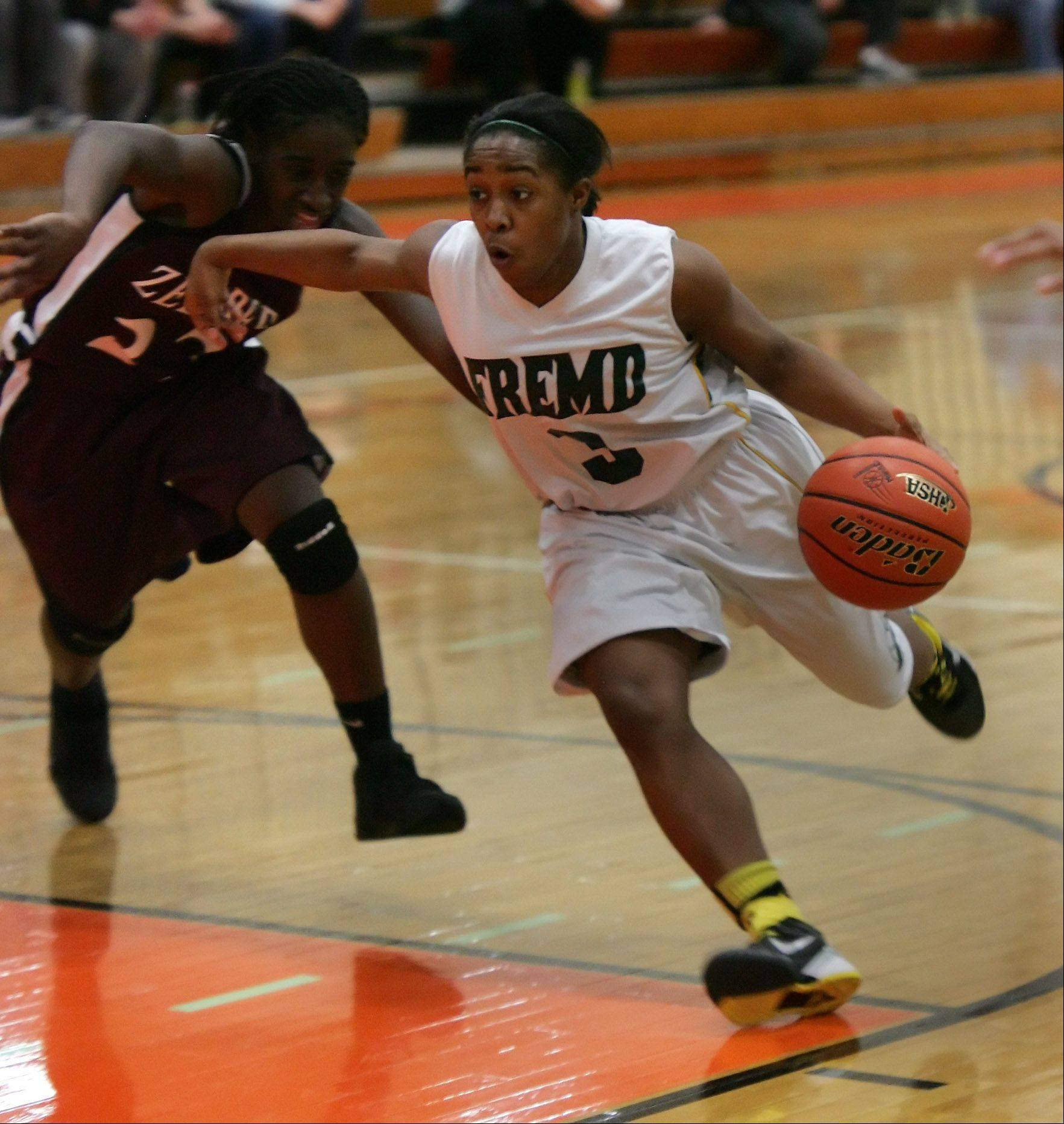 Fremd guard Brianna Lewis drives around Zion-Benton player T.T. Maggett during the girls basketball game between Fremd and Zion-Benton in the Class 4A sectional semifinals at Libertyville High School Monday.
