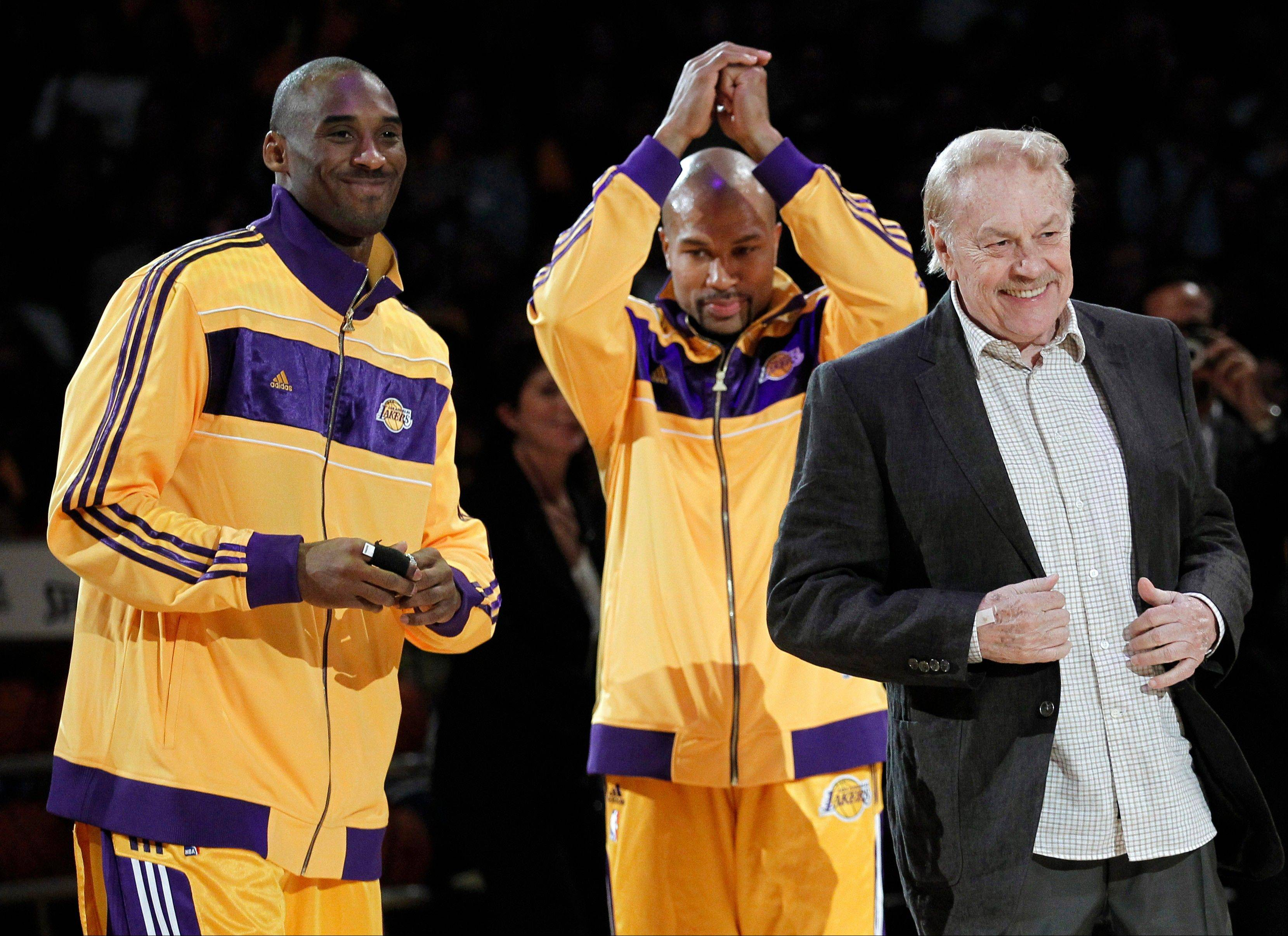 Los Angeles Laker owner Jerry Buss, right, walks out onto the court during the NBA championship ring ceremony as Kobe Bryant, left, and Derek Fisher look on. Buss, the Lakers� playboy owner who shepherded the NBA franchise to 10 championships, has died. He was 80. Bob Steiner, an assistant to Buss, confirmed Monday that Buss had died in Los Angeles.