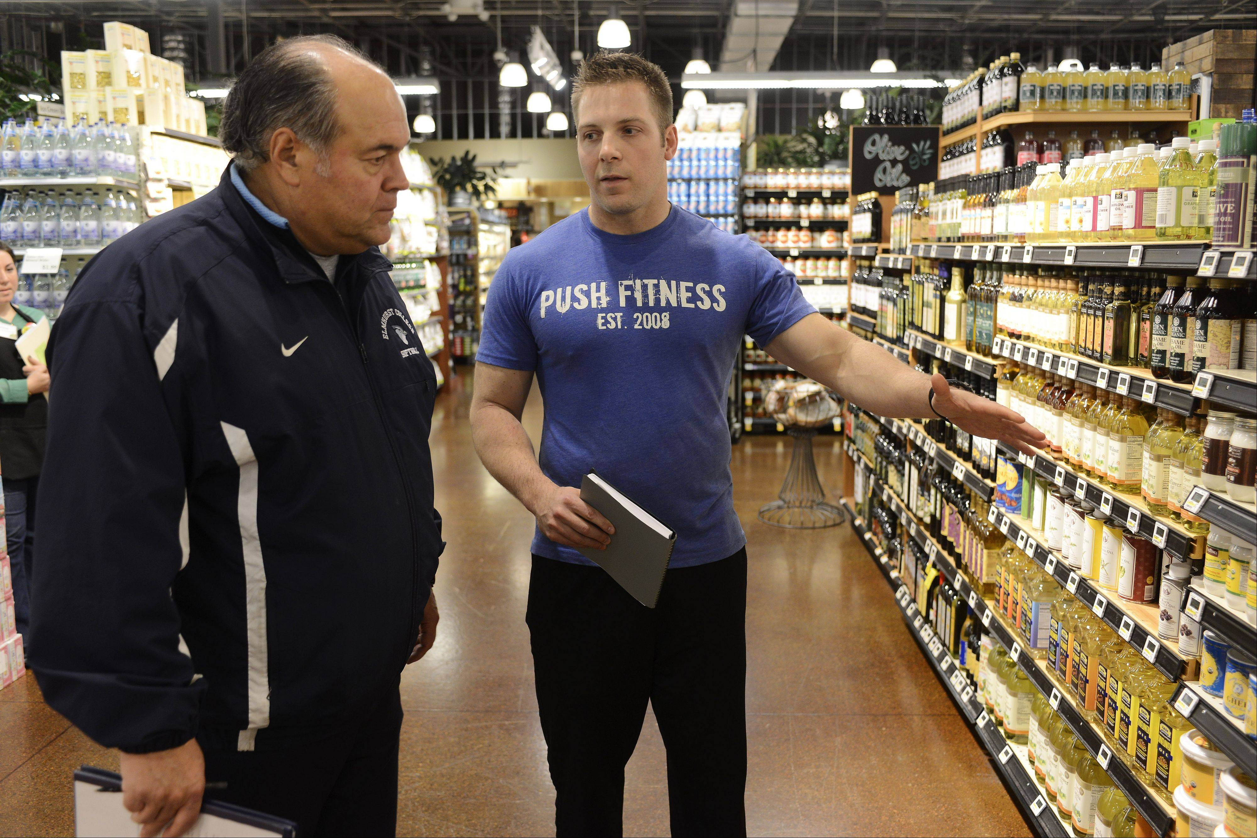 Push Fitness trainer Brodie Medlock points out healthy food options to Mike Paulo at the Whole Foods store in Schaumburg.