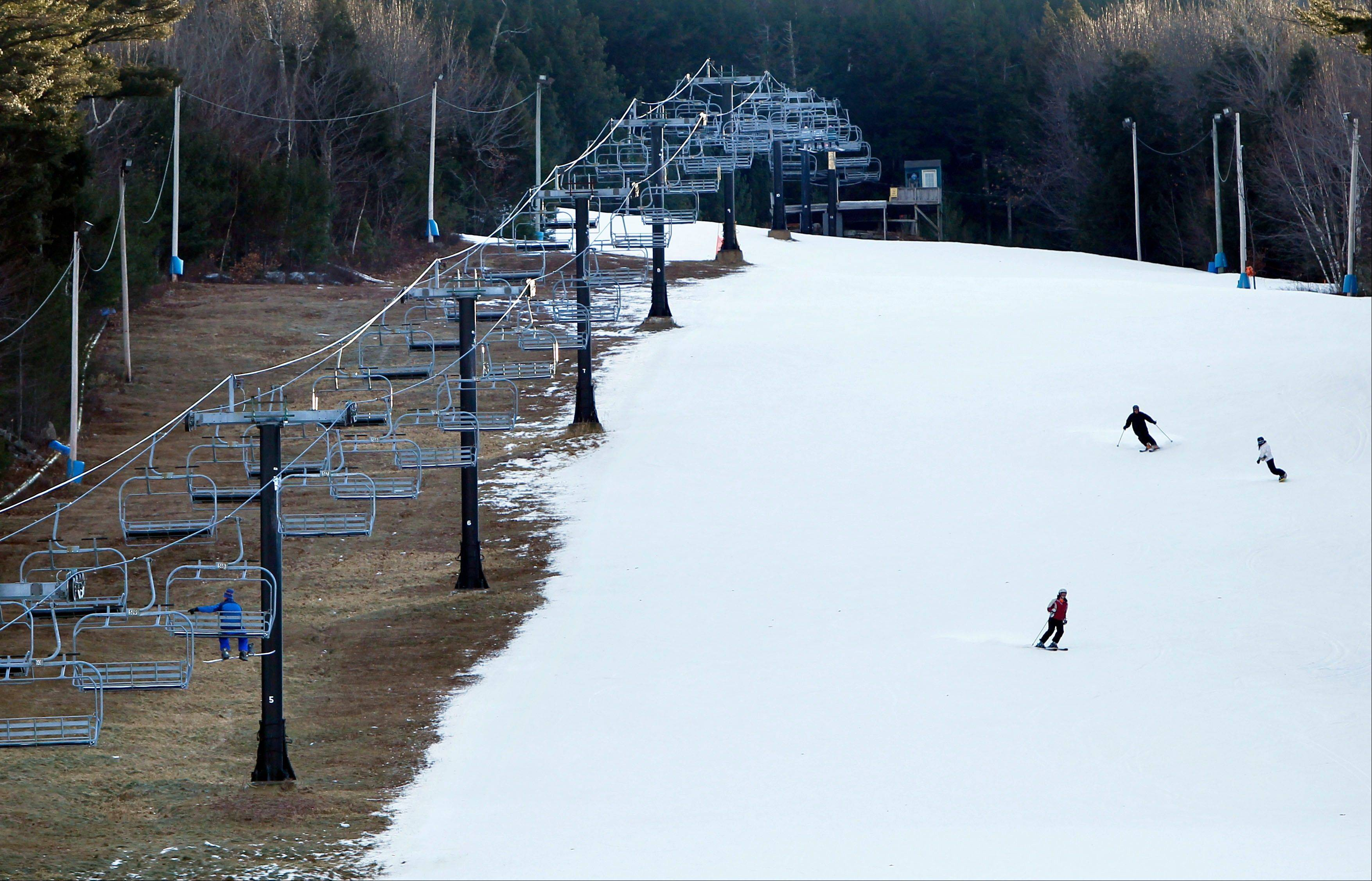 Man-made snow coats a ski run next to barren ground under a chairlift at Shawnee Peak ski area in Bridgton, Maine. Scientists point to both scant recent snowfall in parts of the country and this month's whopper of a Northeast blizzard as potential global warming signs. It may seem like a contradiction, but the explanation lies in atmospheric physics.