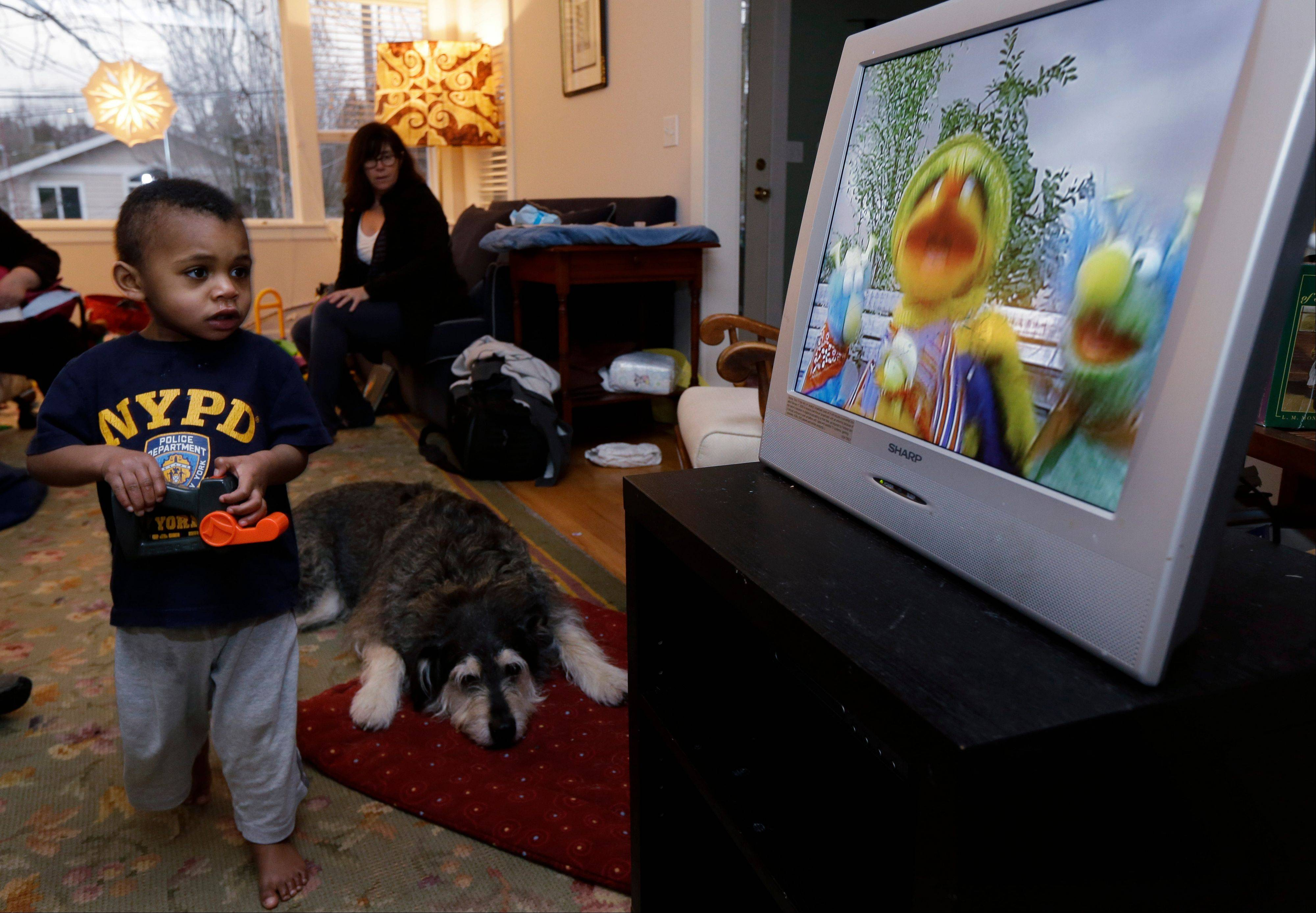 Nancy Jensen, second from left, looks on as her son Joe, 2, is given a special treat of a little TV time at their home in Seattle.
