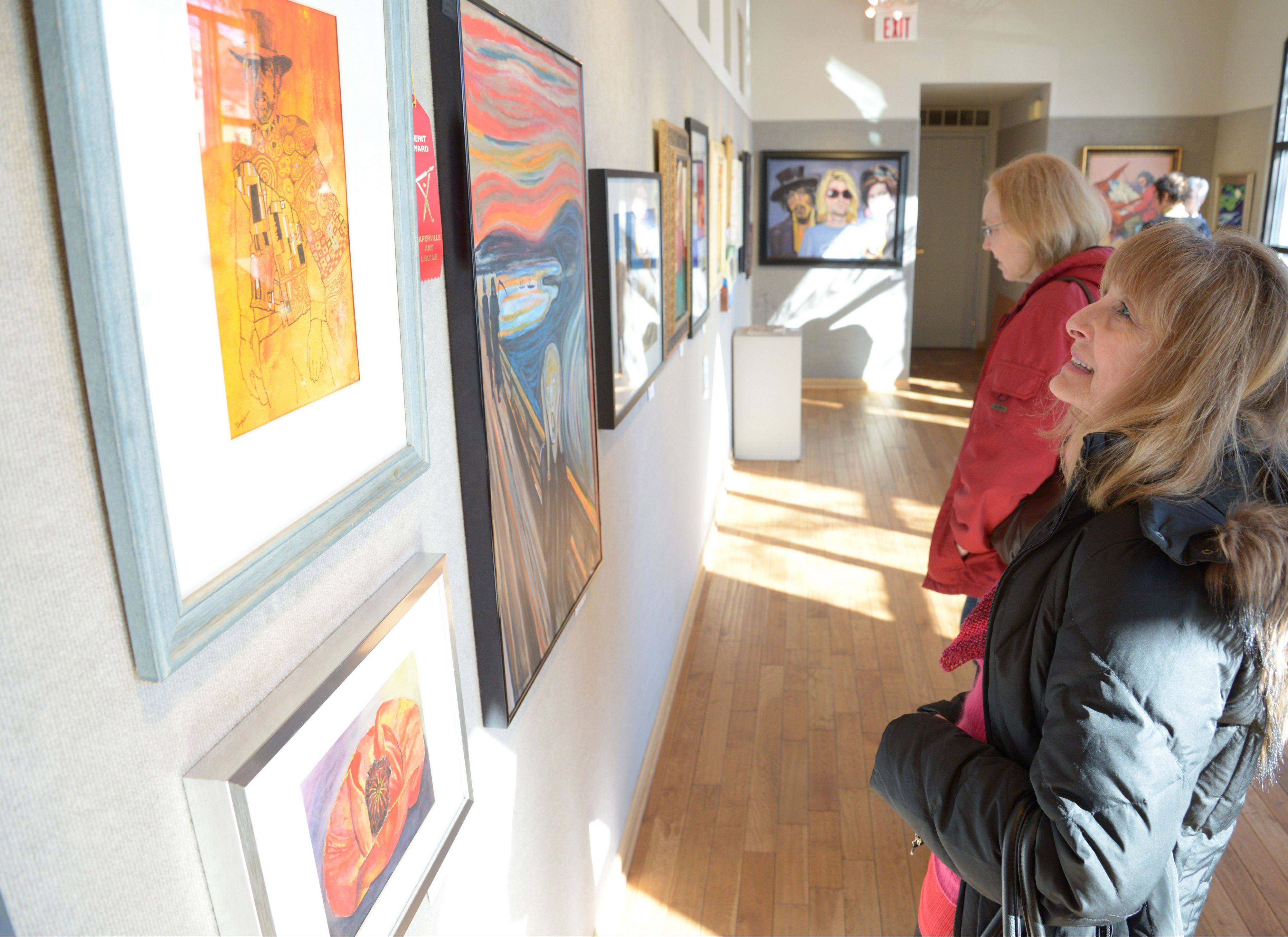 "Rita Moon Kin, of Aurora, gets an eyeful of art during the ""Fabulous Fakes"" show Sunday at the Naperville Fine Art Center and Gallery in Naperville. The exhibit runs through March 2."