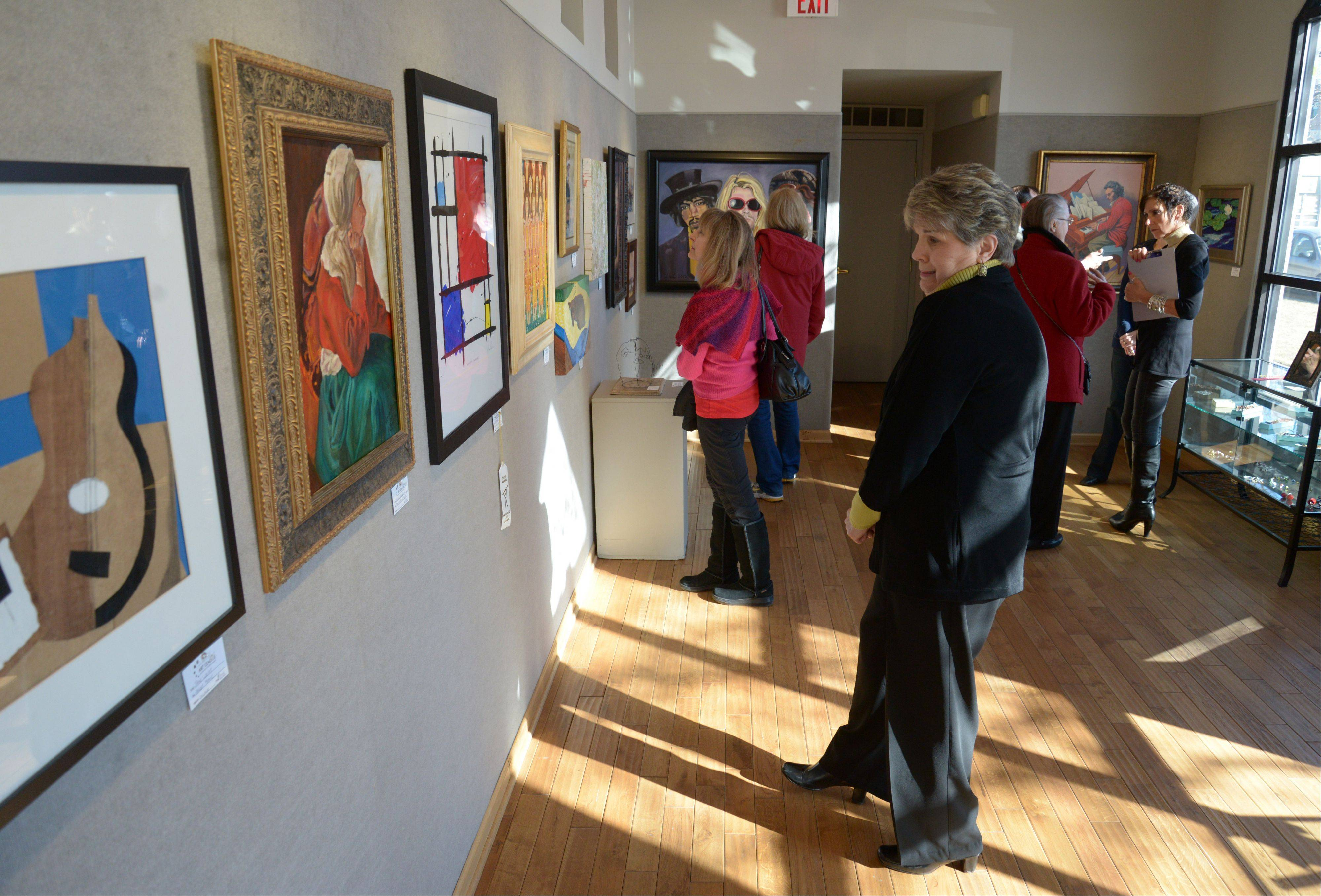 "Art fans look over the work on display Sunday at the ""Fabulous Fakes"" show at the Naperville Fine Art Center and Gallery. The exhibit runs through March 2."