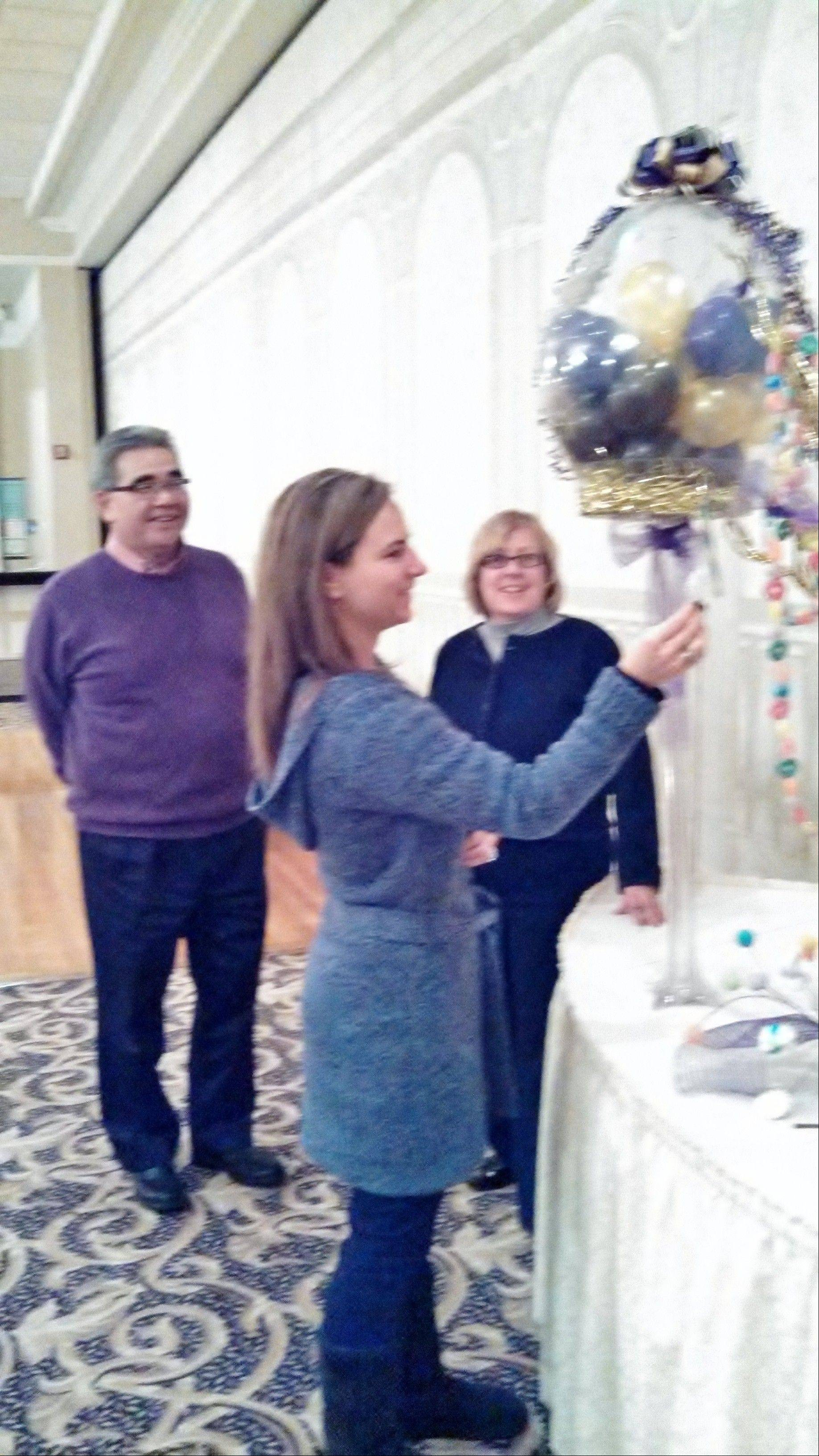 Loralee Pearson puts the finishing touches on table center pieces for the St. Isidore Auction/Dinner Dance Gala on Feb. 23, at the Abbington, in Glen Ellyn. Looking on are gala chairmen Randy and Debbie Isoda. The annual event raises in excess of $65,000 in support of the school.