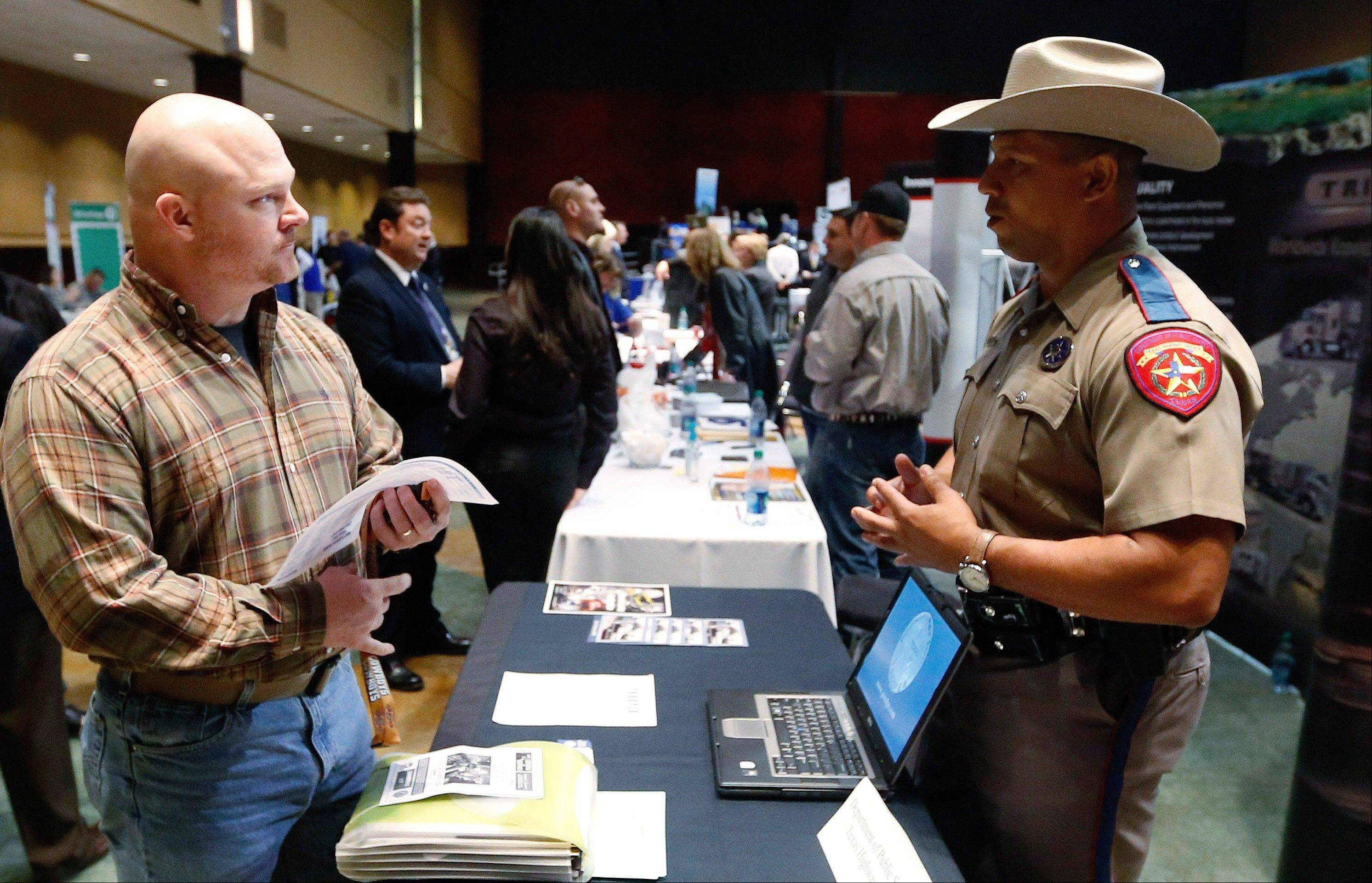 Job Seeker Brett Culver, left, of Newalla, Okla., formerly of the Air Force, talks with Texas state trooper Deon Cockrell, right, at a Recruit Military job fair in Oklahoma City.