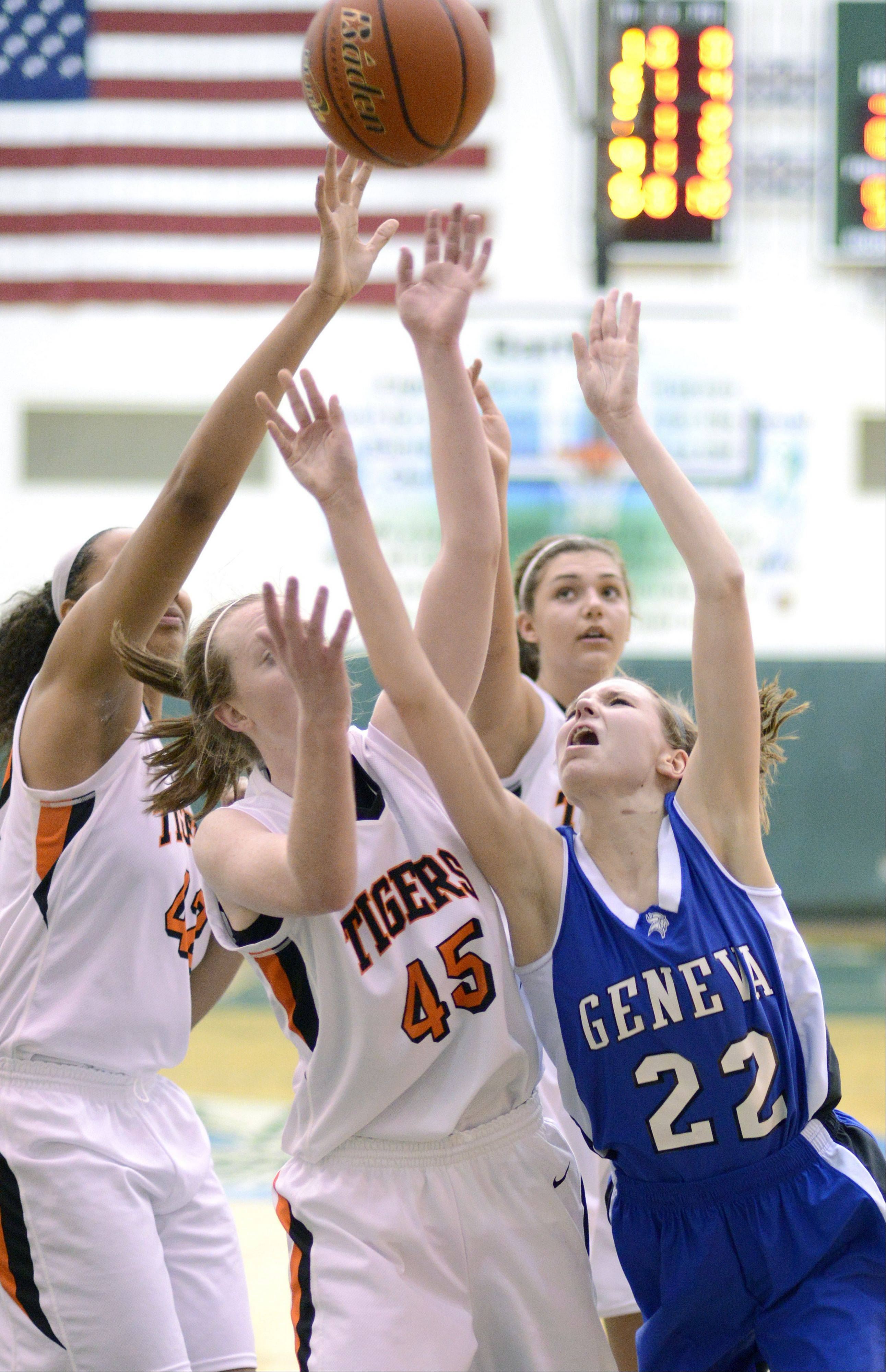 Geneva's Morgan Seberger jumps for a rebound with Wheaton Warrenville South's Diamond Thompson and Meghan Waldron in the second quarter of the Class 4A sectional semifinals on Tuesday, February 19.