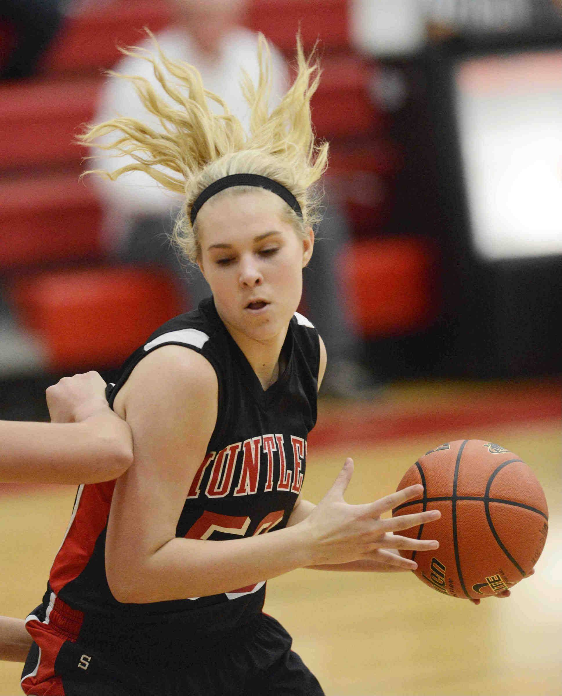 Huntley's Ali Andrews, left, controls the baskteball against Harlem Tuesday night at the Class 4A Rockford East sectional.