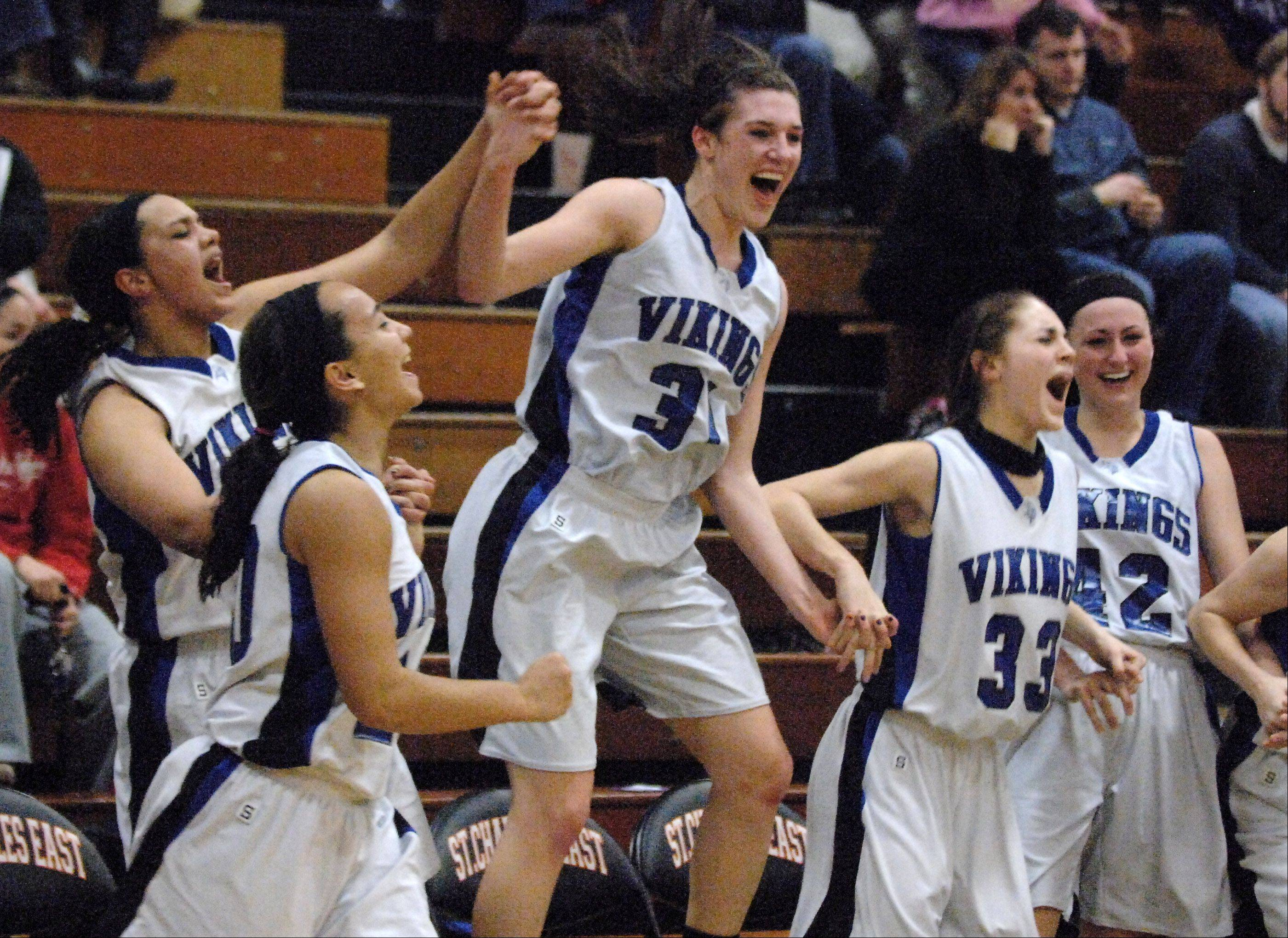 Geneva's Sami Pawlak, 31, and her teammates celebrate in the final seconds of their win over St. Charles East during Thursday's regional final game in St. Charles.