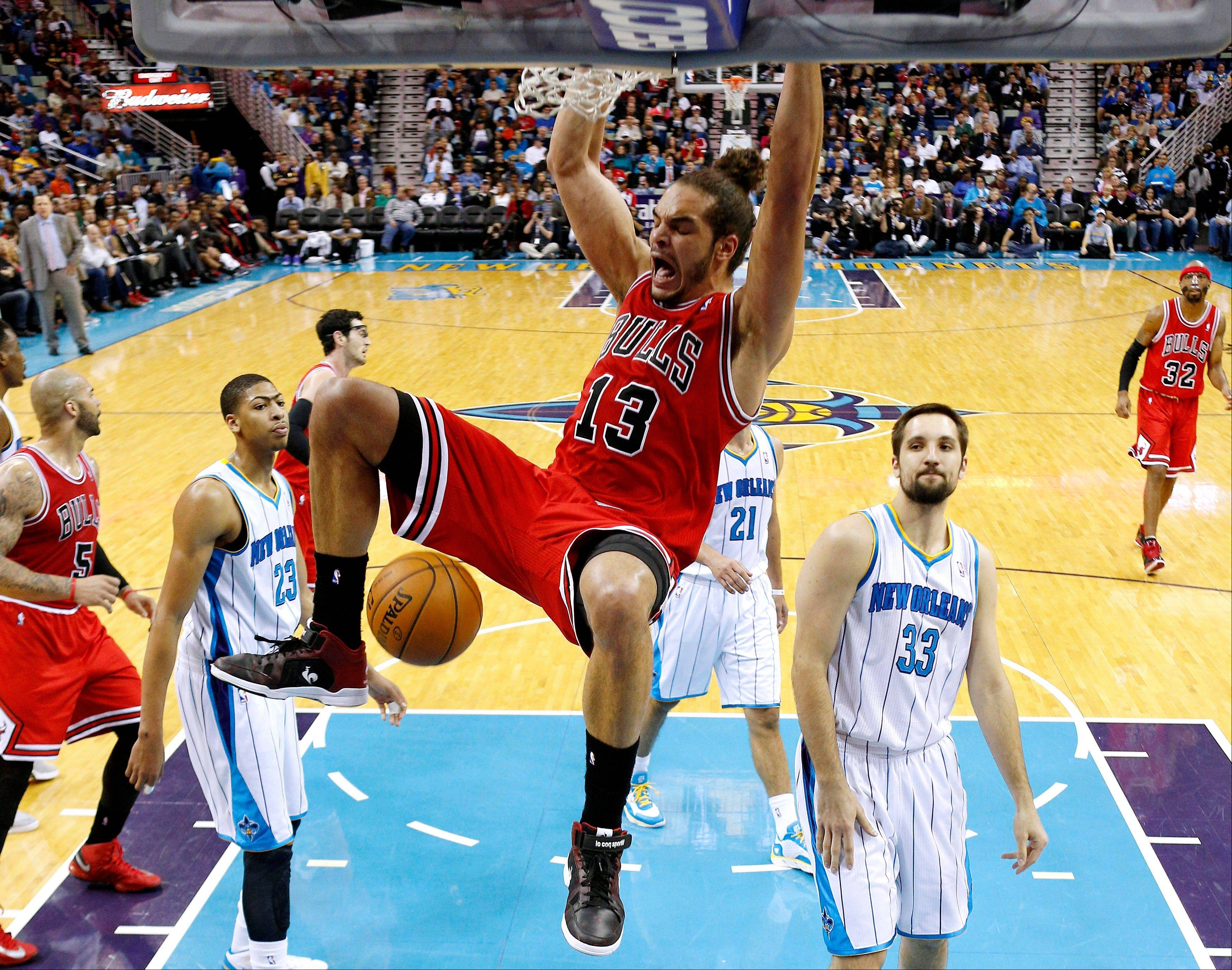 Chicago Bulls center Joakim Noah (13) dunks over New Orleans Hornets forwards Ryan Anderson (33) and Anthony Davis (23) during the second half of an NBA basketball game in New Orleans Tuesday.