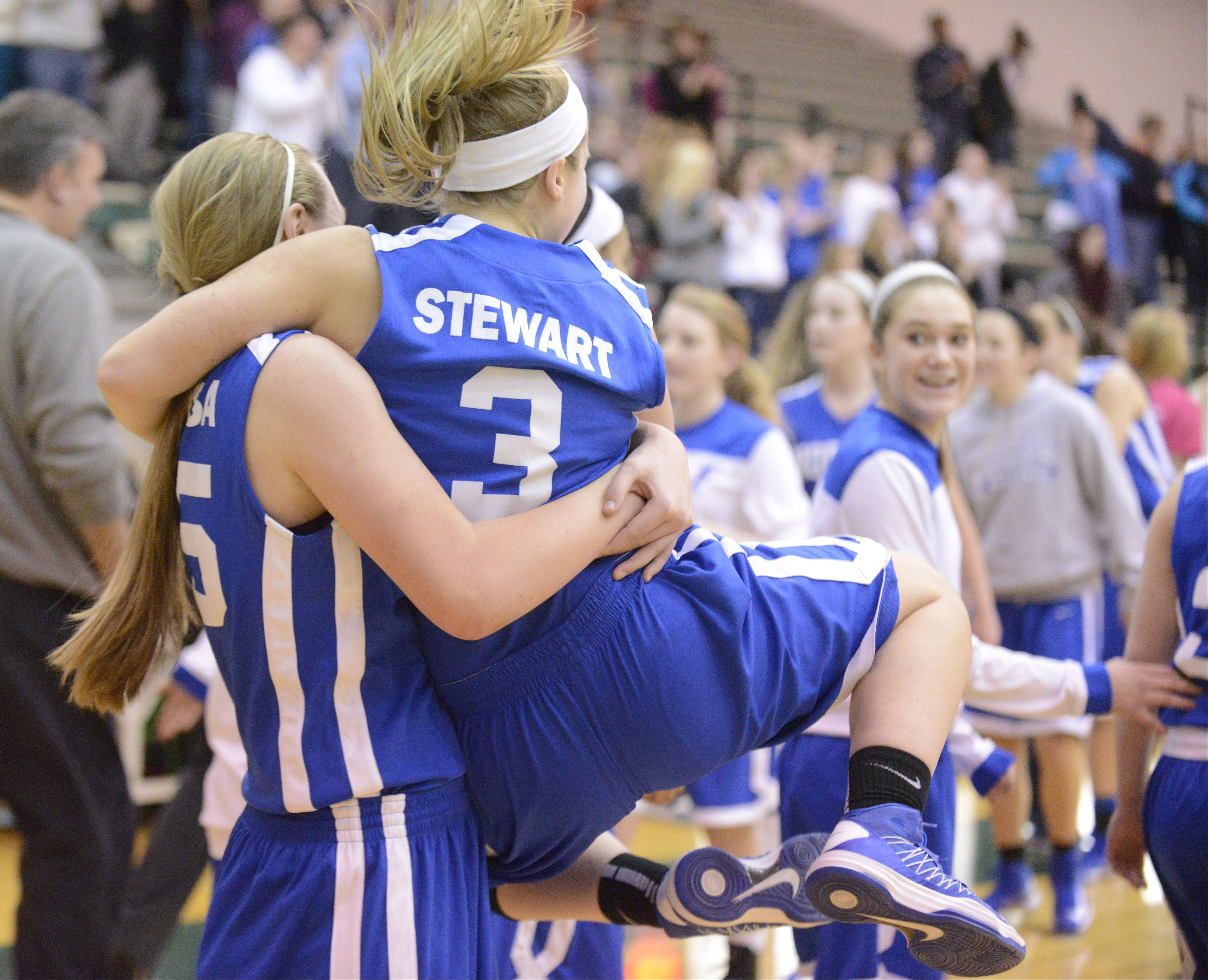 Wheaton North's Mandy Traversa lifts teammate Reilly Stewart as she clicks her heels after their win over Schaumburg.