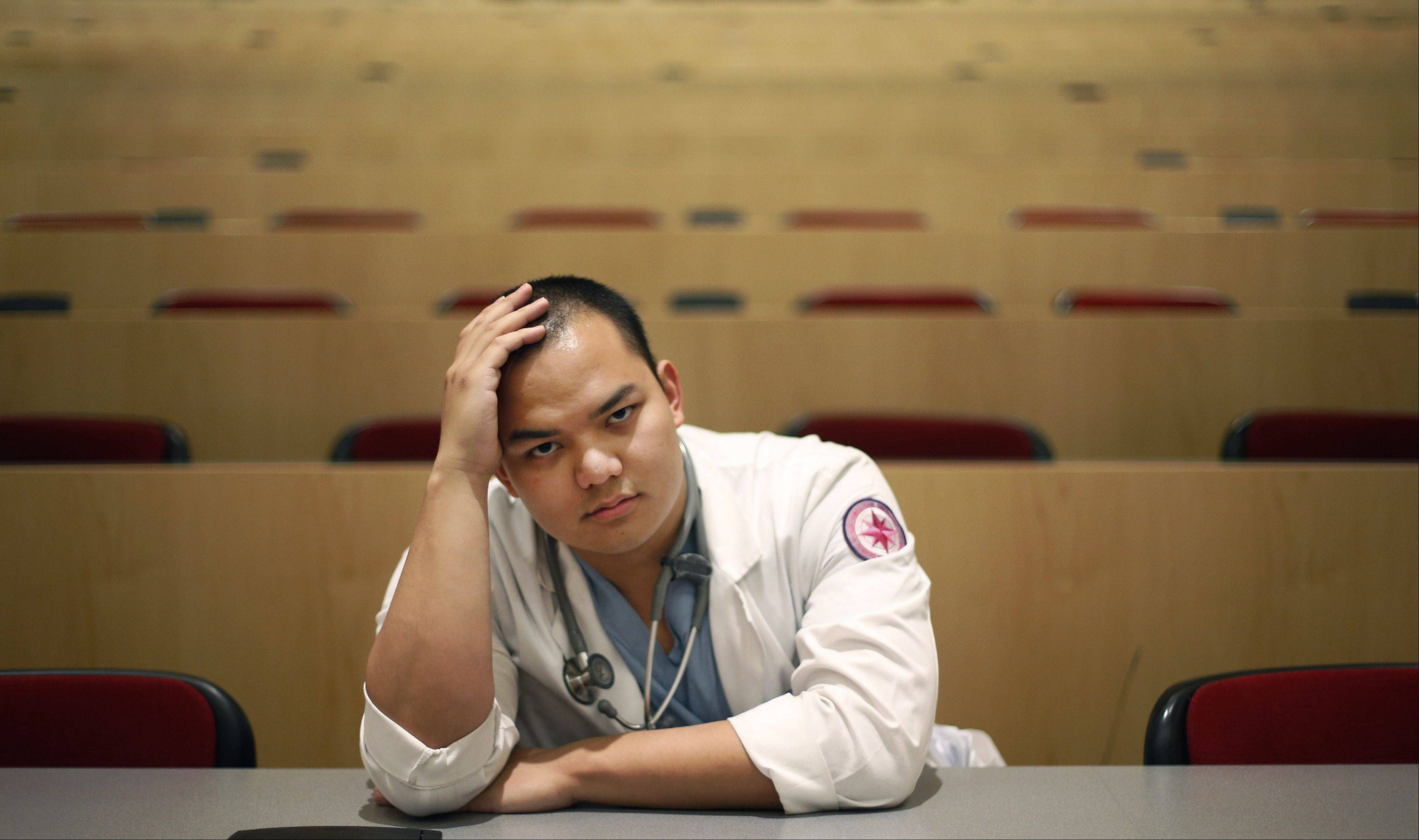 Marc Lim, a senior medical student at Northwestern University's Feinberg School of Medicine, poses in a campus classroom Tuesday in Chicago. Hundreds of medical students like Lim may not be able to start their residency programs in Illinois this summer because of imminent licensing delays.