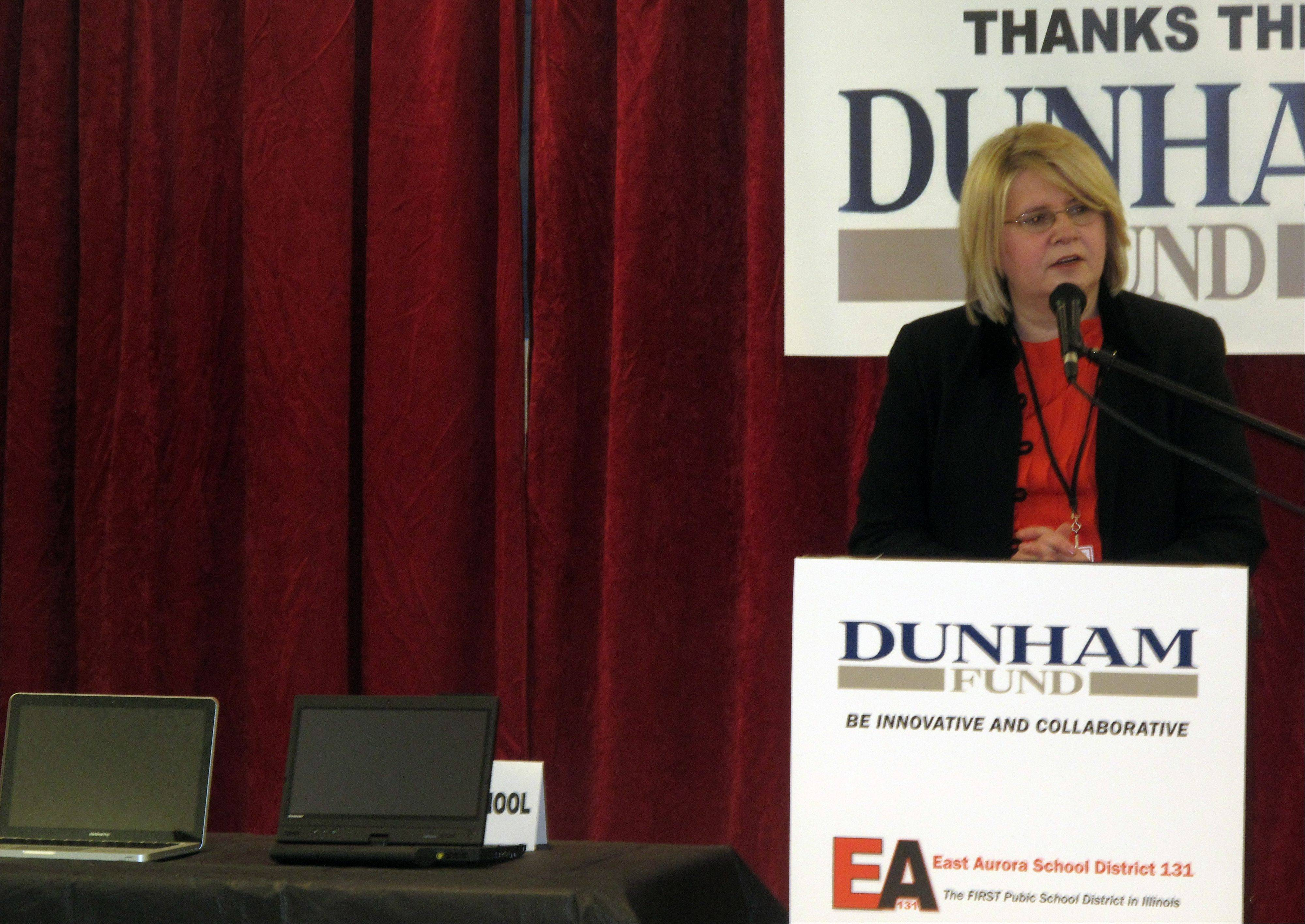 Annette Johnson, president of the East Aurora District 131 school board, discusses the laptops the district will buy for each student in its magnet academy using a $660,000 grant from the Dunham Fund. MacBook Pros will be given to seventh- and eighth-grade students, while high schoolers will be given tablet-style laptops.