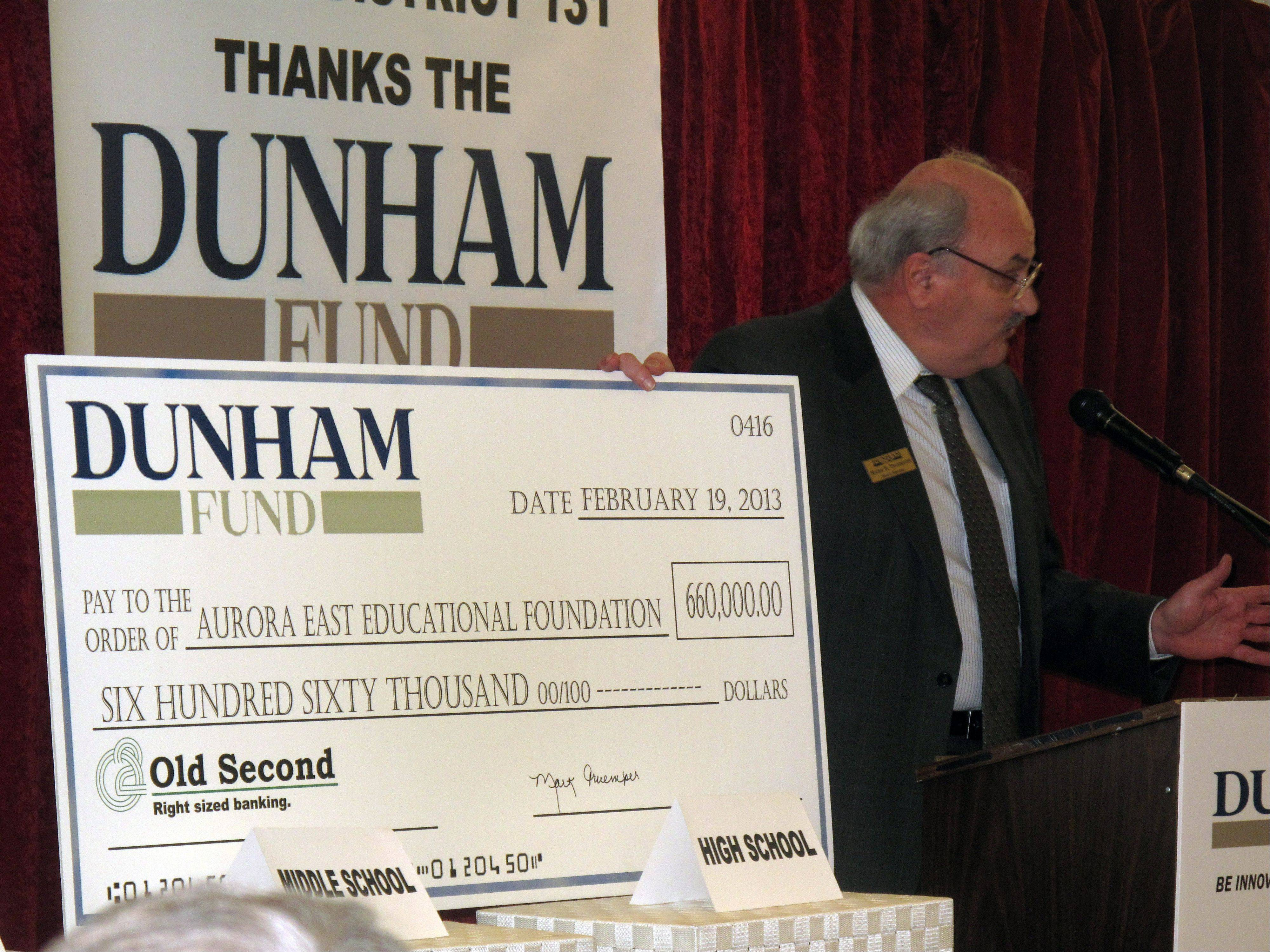 Mark Truemper, a member of the Dunham Fund's board of directors, gives a $660,000 grant Tuesday to East Aurora District 131 so each of 750 students at the district's Fred Rodgers Magnet Academy can receive a personal laptop next year.