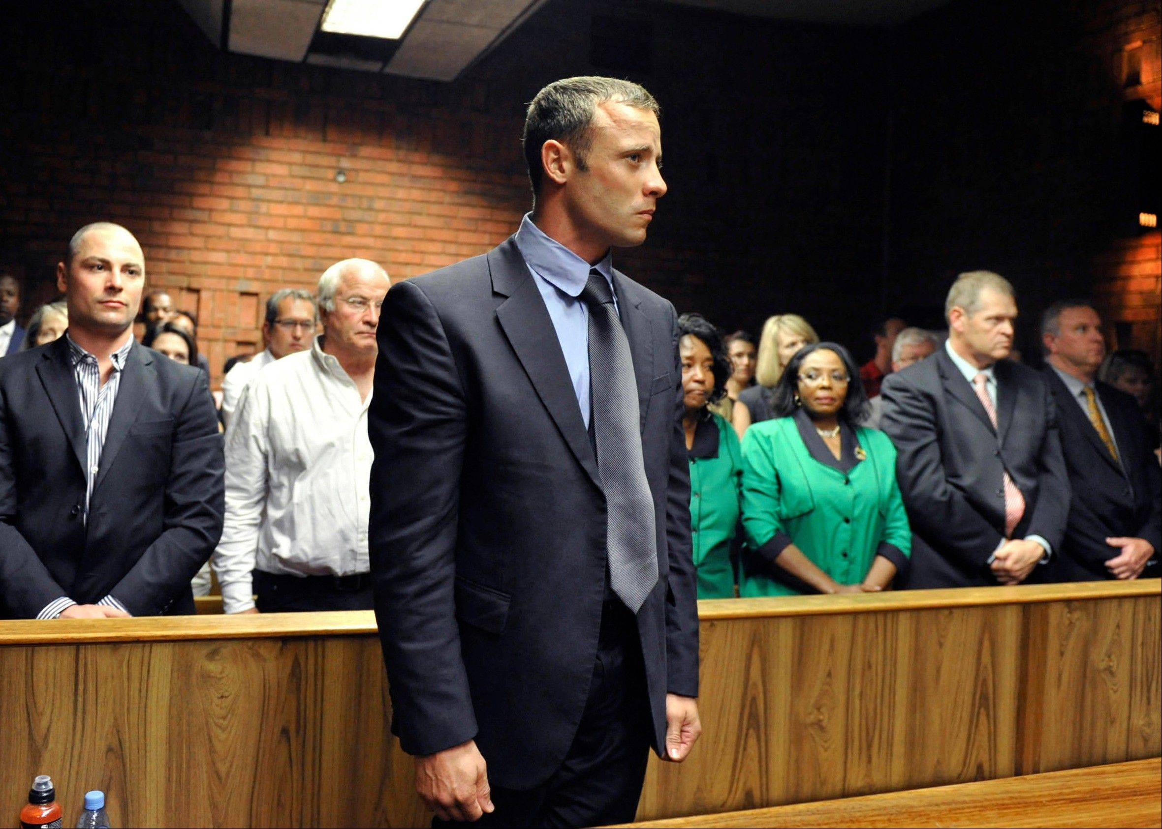 Olympian Oscar Pistorius stands following his bail hearing in Pretoria, South Africa, Tuesday. Pistorius fired into the door of a small bathroom where his girlfriend was cowering after a shouting match on Valentine's Day, hitting her three times, a South African prosecutor said Tuesday as he charged the sports icon with premeditated murder.