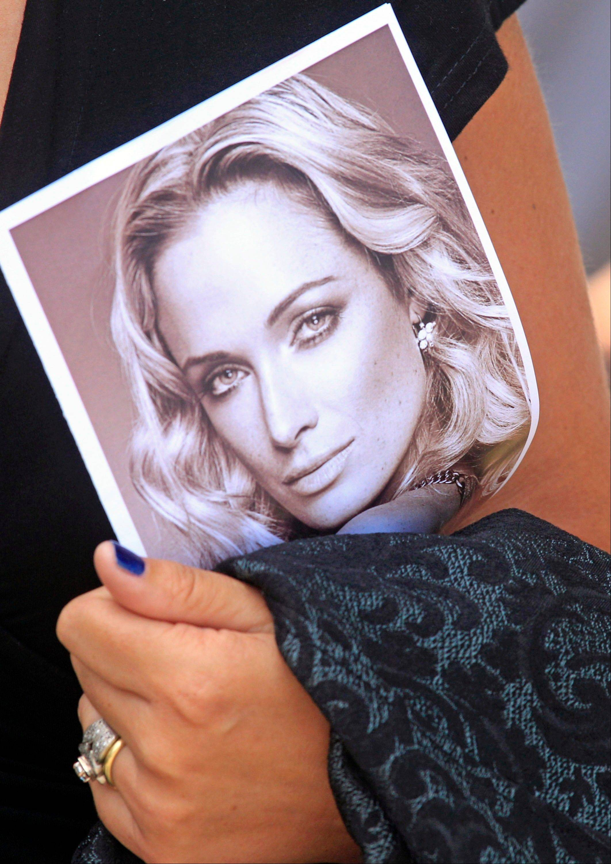 A woman holds a photo of Reeva Steenkamp, as she leaves her funeral in Port Elizabeth, South Africa, Tuesday. Olympic athlete Oscar Pistorius is charged with the premeditated murder of Steenkamp on Valentine's Day. The defense lawyer says it was an accidental shooting.