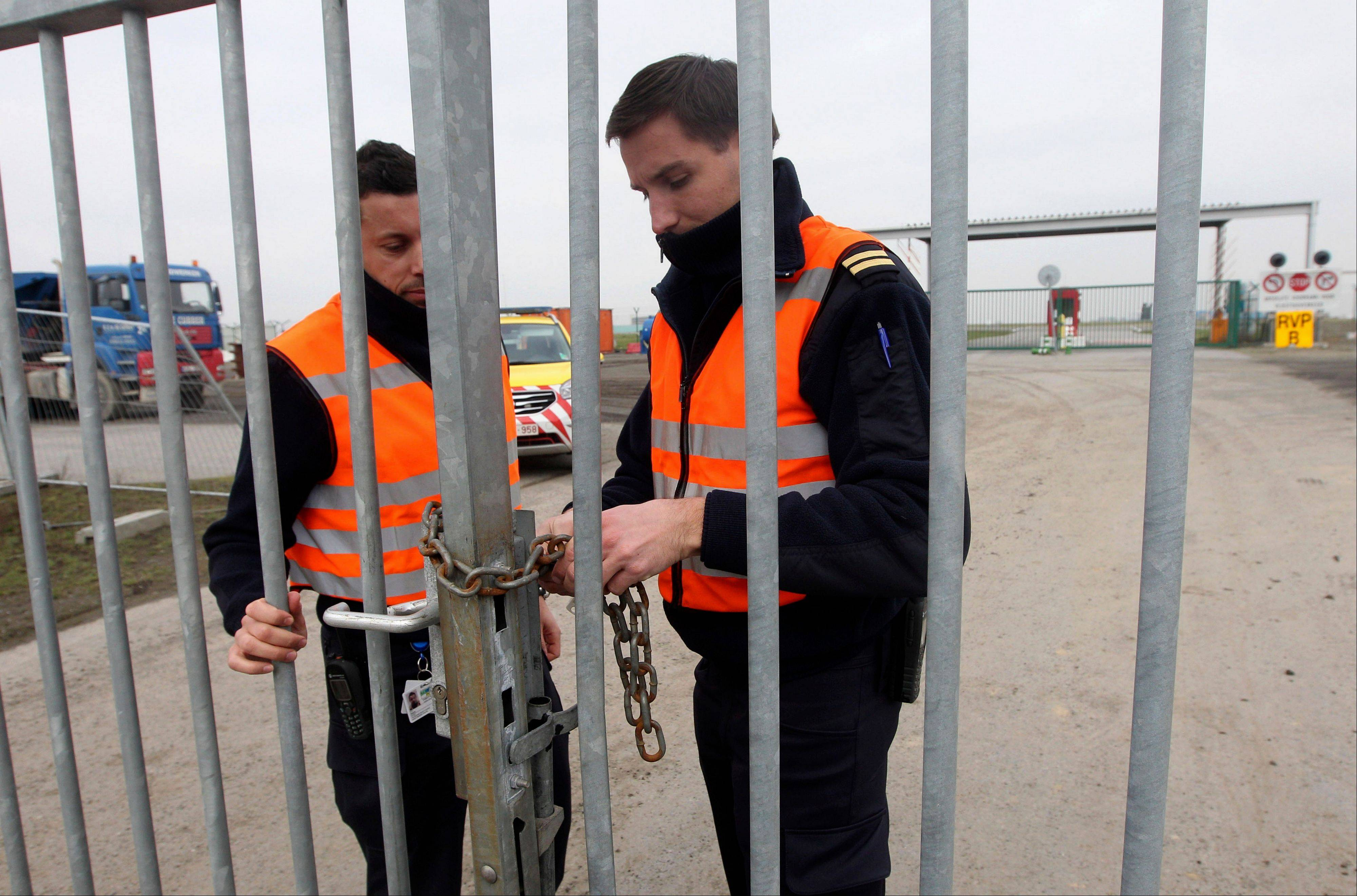 Two airport police officers use a chain to lock a gate which leads to the airport tarmac, at Brussels international airport, Tuesday, Feb. 19, 2013. Eight masked gunmen made a hole in a security fence at Brussels' international airport, drove onto the tarmac and snatched some $50 million worth of diamonds from the hold of a Swiss-bound plane without firing a shot, authorities said Tuesday.