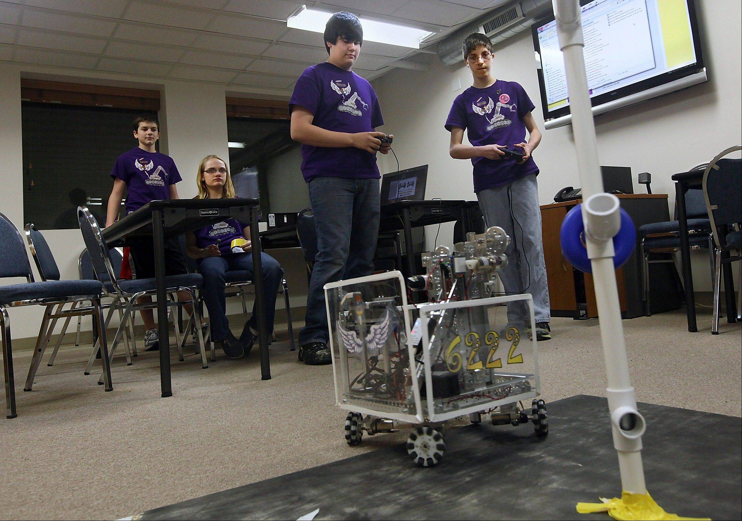 Associated PressHome-schooled students Andrew Lukens, center, and Joshua Wiley, right, operate a robot with game controllers as they try to get rings off one side of the pole and move the robot around the pole and replace the rings on the opposite side in Quincy.