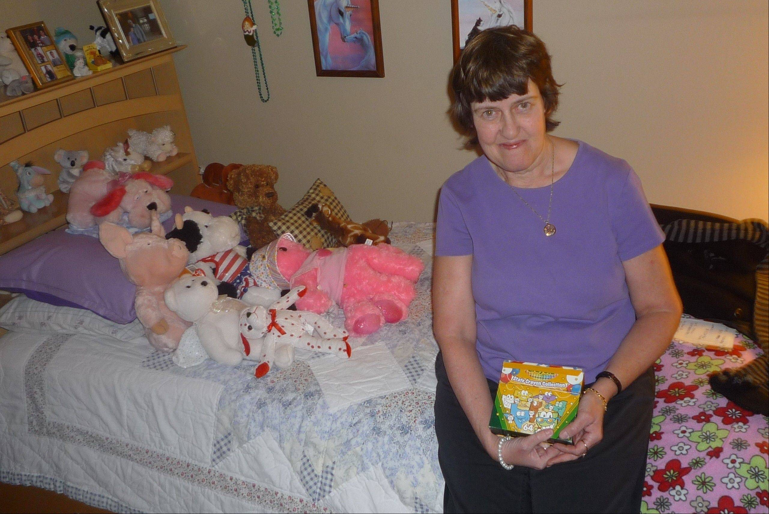 Showing off a box of crayons in her bedroom she decorates with stuffed animals and unicorn drawings, Cindy Moore lives as independently as she can with her developmental disability.
