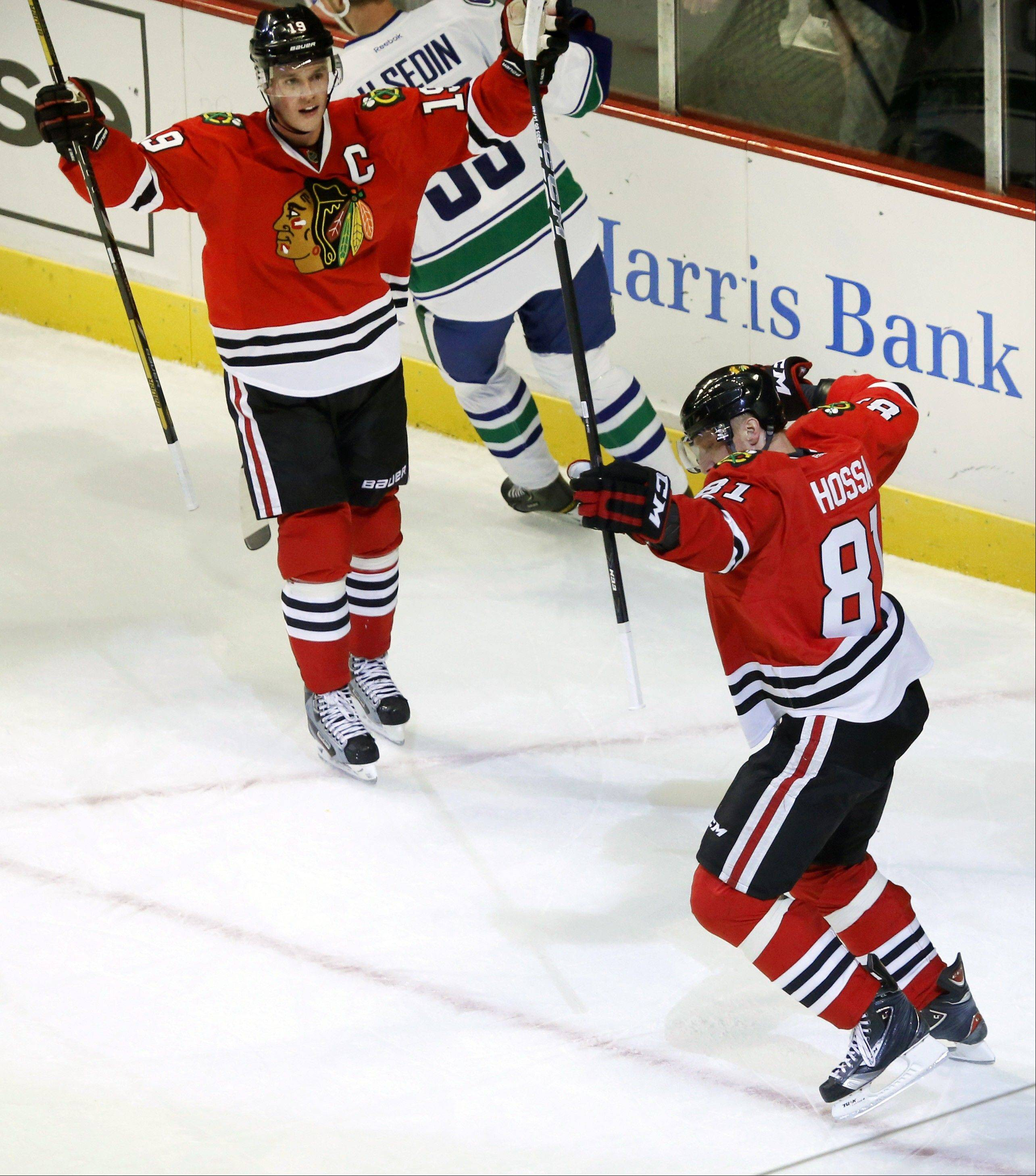 Chicago Blackhawks right wing Marian Hossa (81), from Slovakia, celebrates his second goal of the game with Jonathan Toews (19) during the second period of an NHL hockey game against the Vancouver Canucks Tuesday, Feb. 19, 2013 in Chicago.