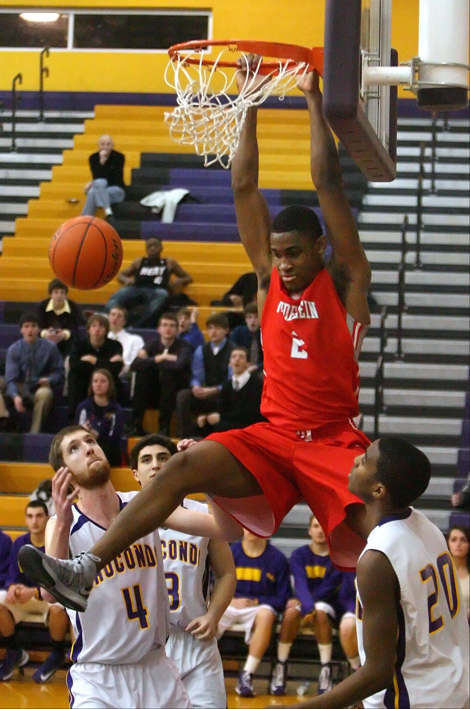 Mundelein's Chino Ebube goes in for the dunk over Wauconda's Ricky Sidlowski, left, and Devon King during Wednesday's game in Wauconda.