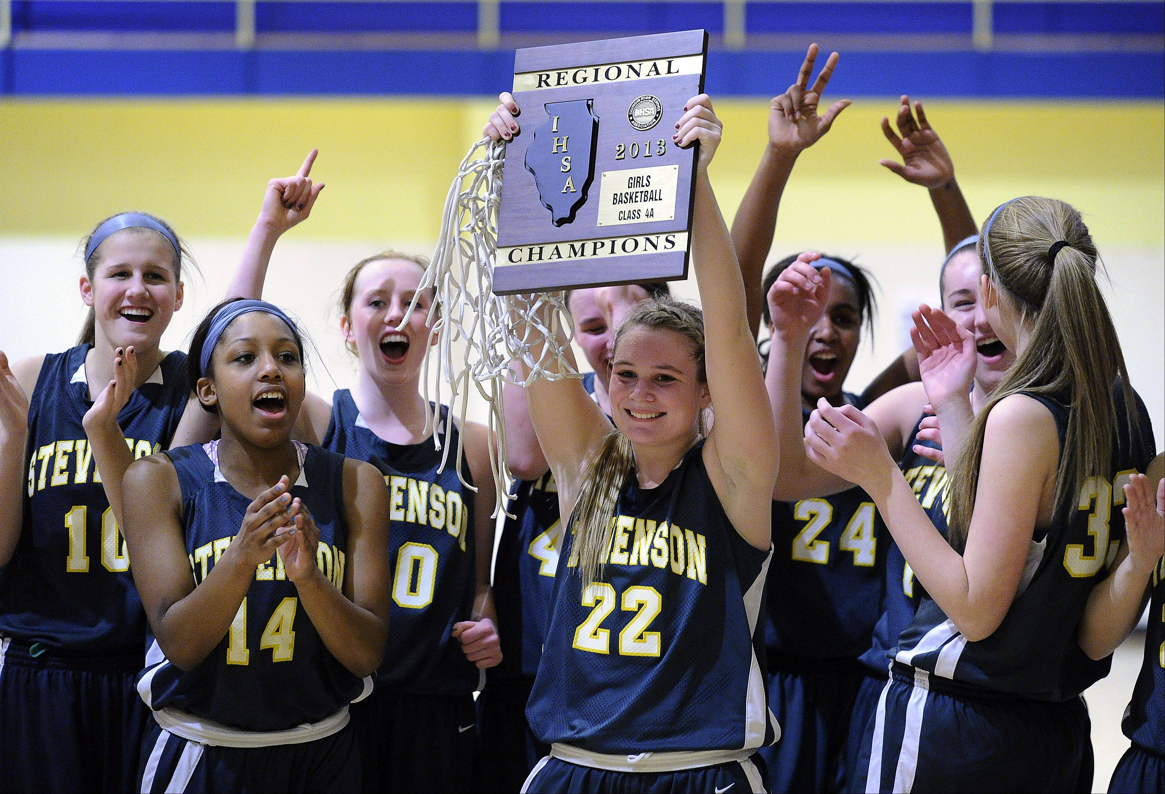Stevenson's Kari Moffat holds up the Class 4A regional championship plaque while her teammates celebrate after defeating Palatine in Thursday's game in Wheeling.