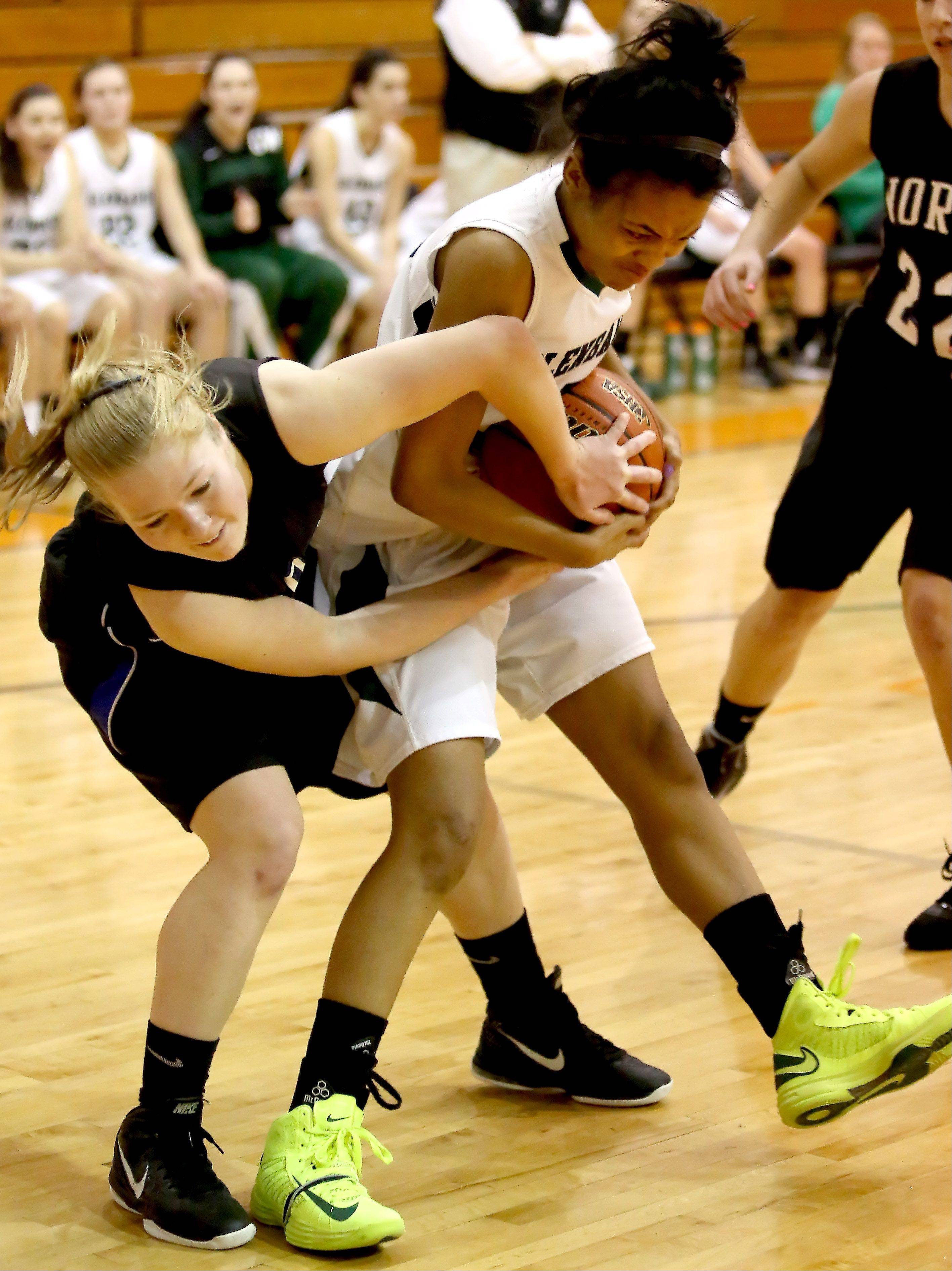 St. Charles North's Natalie Winkates, left, and Glenbard West Breanna Venson wrestle for control during Monday's Class 4A regional basketball game.