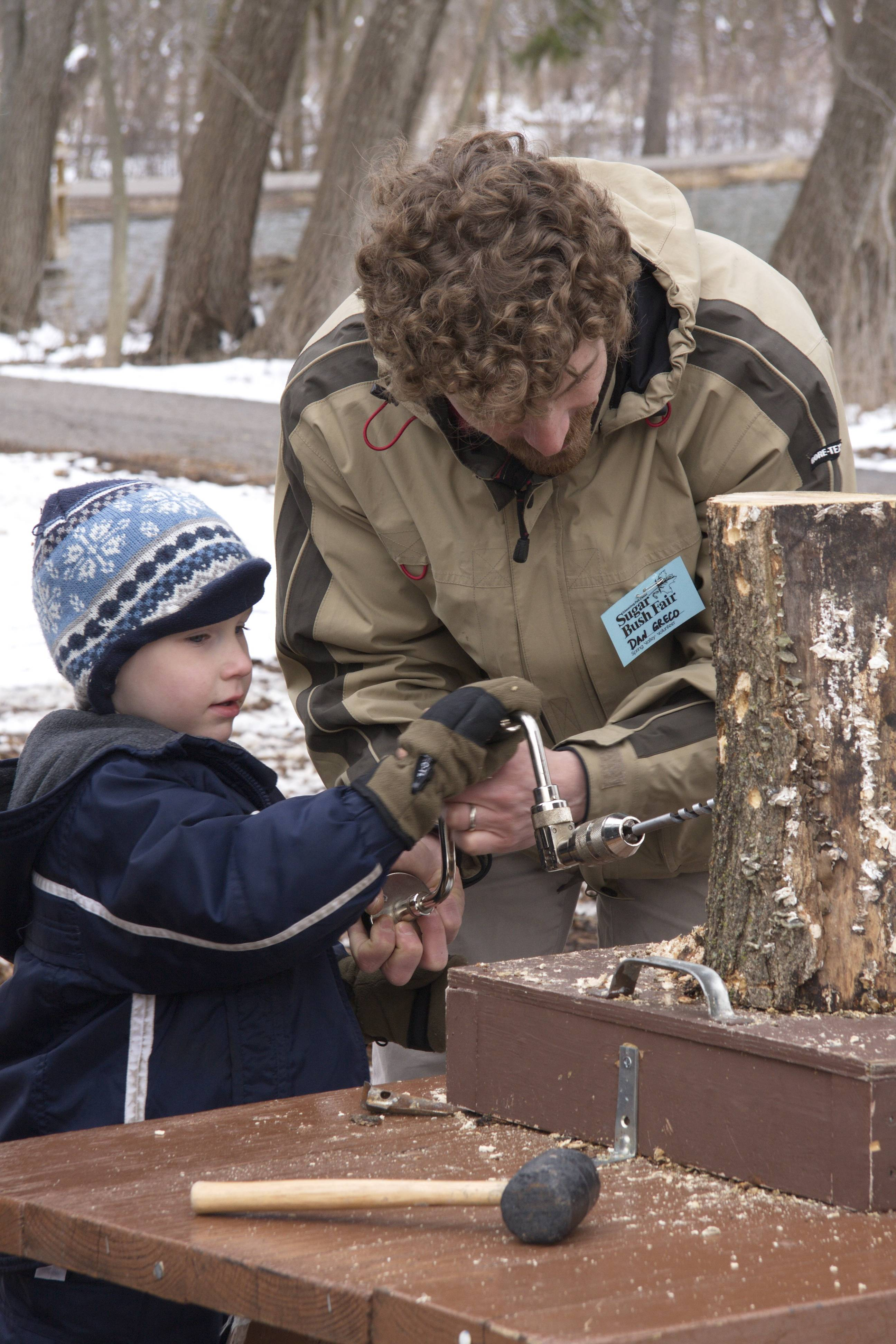 A child and adult work on tapping maple syrup at Spring Valley.