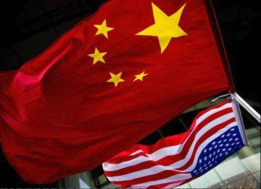 In this Nov. 7, 2012 photo, U.S. and Chinese national flags are hung outside a hotel during the U.S. Presidential election event, organized by the U.S. embassy in Beijing. As public evidence mounts that the Chinese military is responsible for stealing massive amounts of U.S. government data and corporate trade secrets, the Obama administration is eyeing fines and other trade actions it may take .