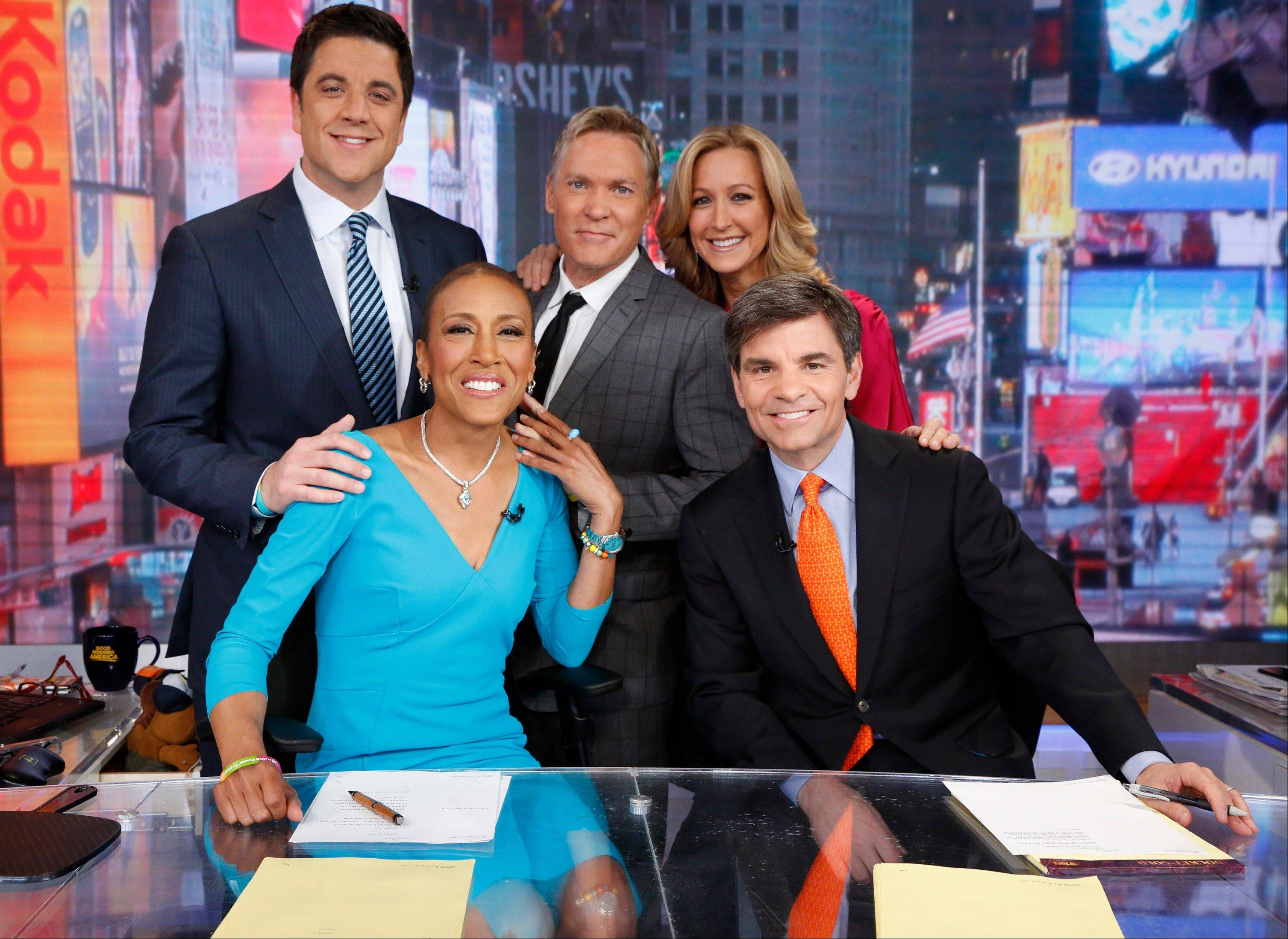 "Robin Roberts, left, George Stephanopoulos, Josh Elliott, Sam Champion and Lara Spencer on the set of ""Good Morning America"" in New York. Five months after undergoing a bone-marrow transplant, Roberts is back on television in the morning."