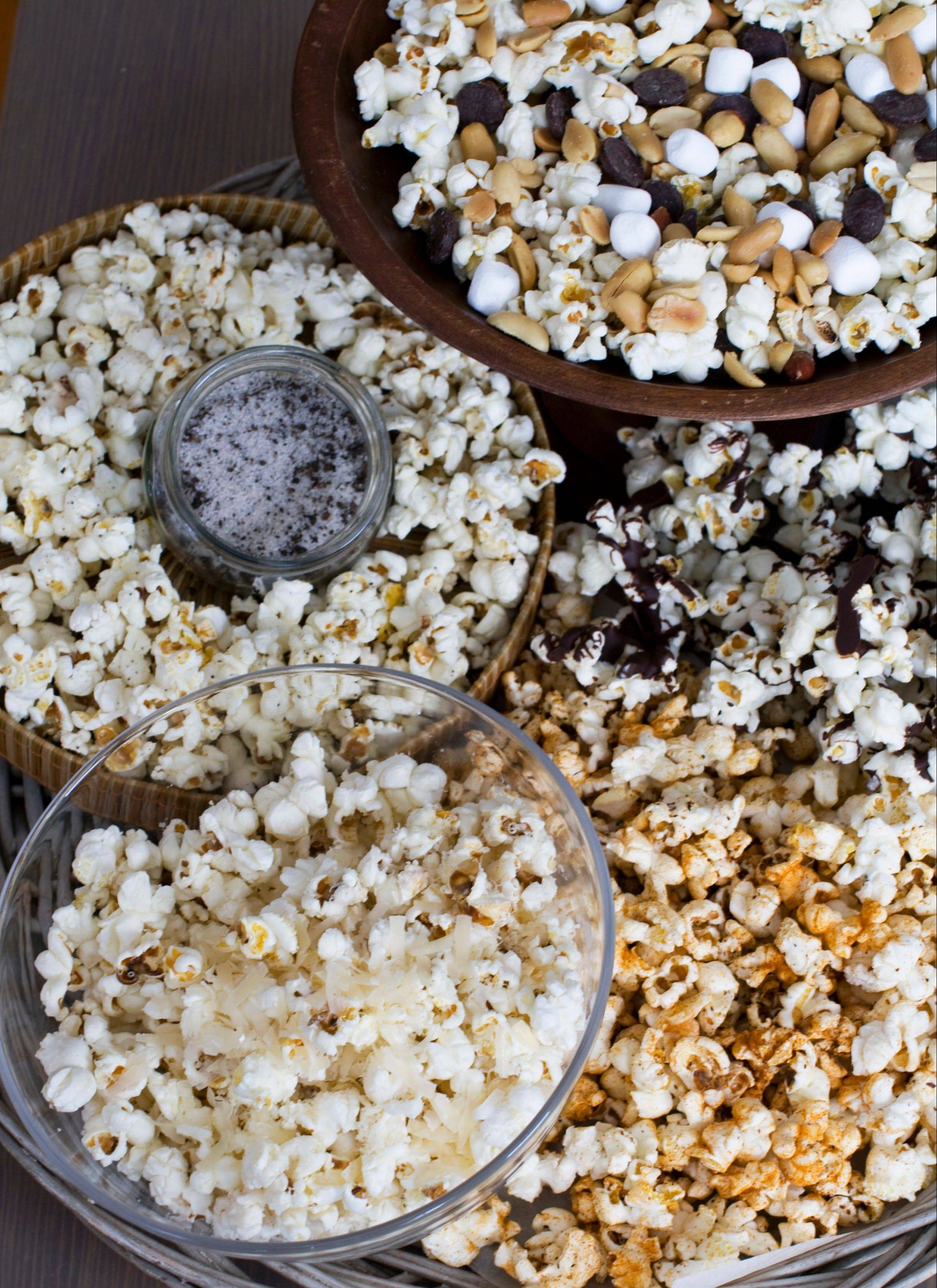 Stovetop Popcorn Many Ways, from top clockwise, mini marshmallows, chocolate chips and salted peanuts, melted chocolate, sweet and spicy barbecue rub, finely grated parmesan cheese, and truffle salt.