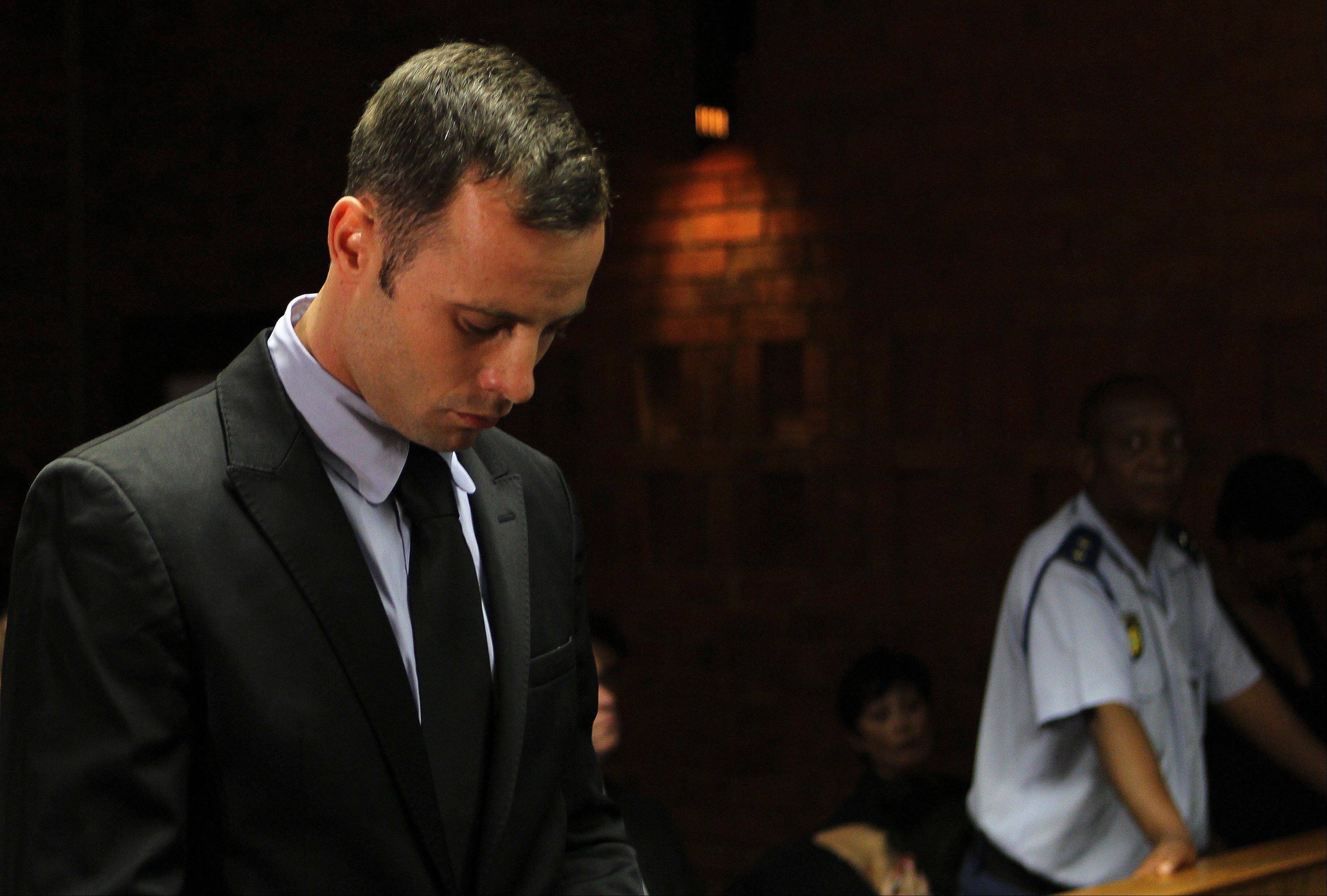 Olympic athlete Oscar Pistorius stands inside the court as a police officer looks on during his bail hearing at the magistrate court in Pretoria, South Africa, Wednesday, Feb. 20, 2013.