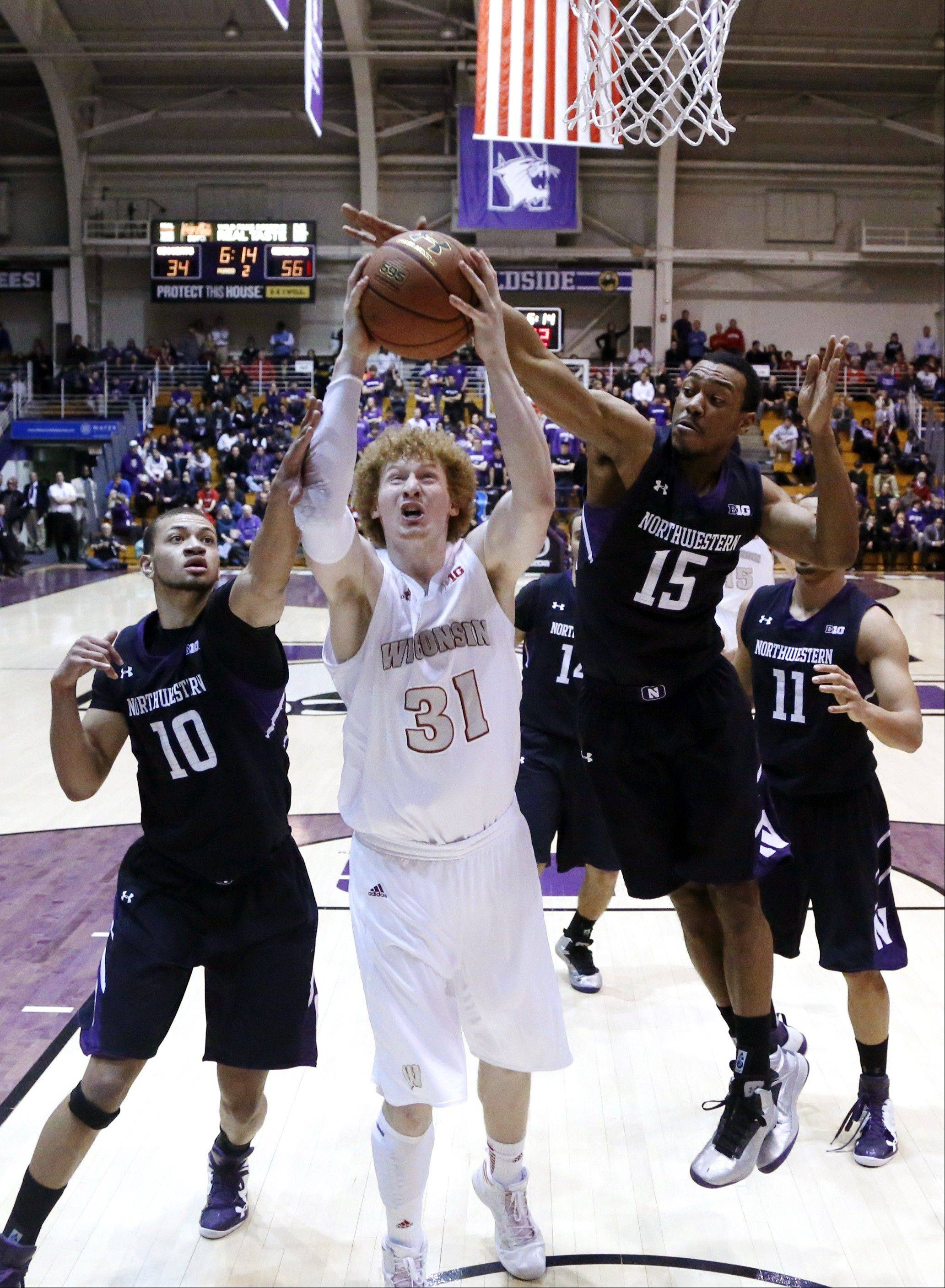 Wisconsin forward Mike Bruesewitz (31) is fouled as he shoots between Northwestern's Mike Turner (10) and James Montgomery III (15) during the second half of an NCAA college basketball game, Wednesday, Feb. 20, 2013, in Evanston, Ill. Wisconsin won 69-41. (AP Photo/Charles Rex Arbogast)