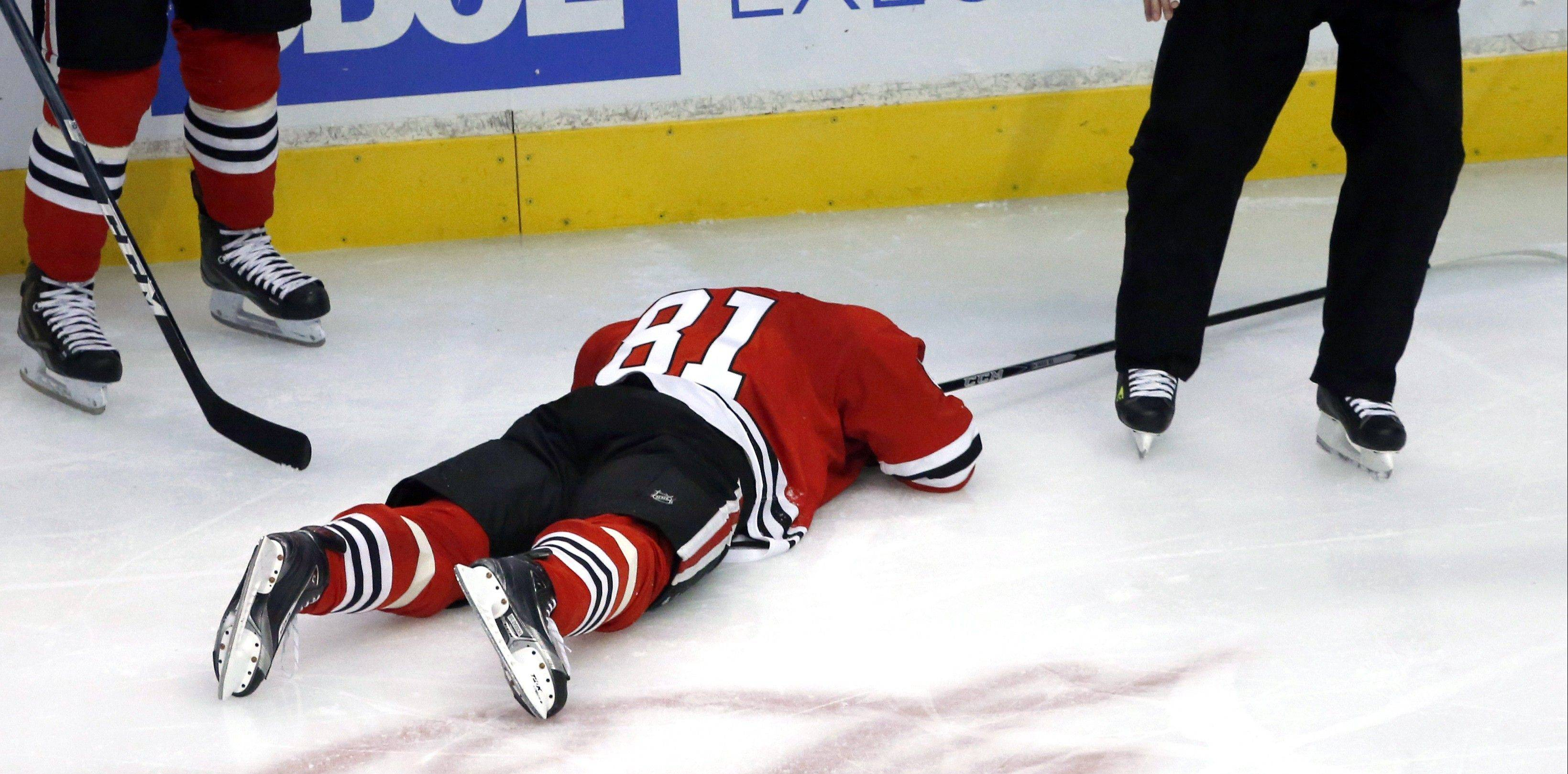 The Blackhawks� Marian Hossa lies on the ice after being hit in the back of the head by Jannik Hansen of the Canucks on Tuesday night at the United Center.