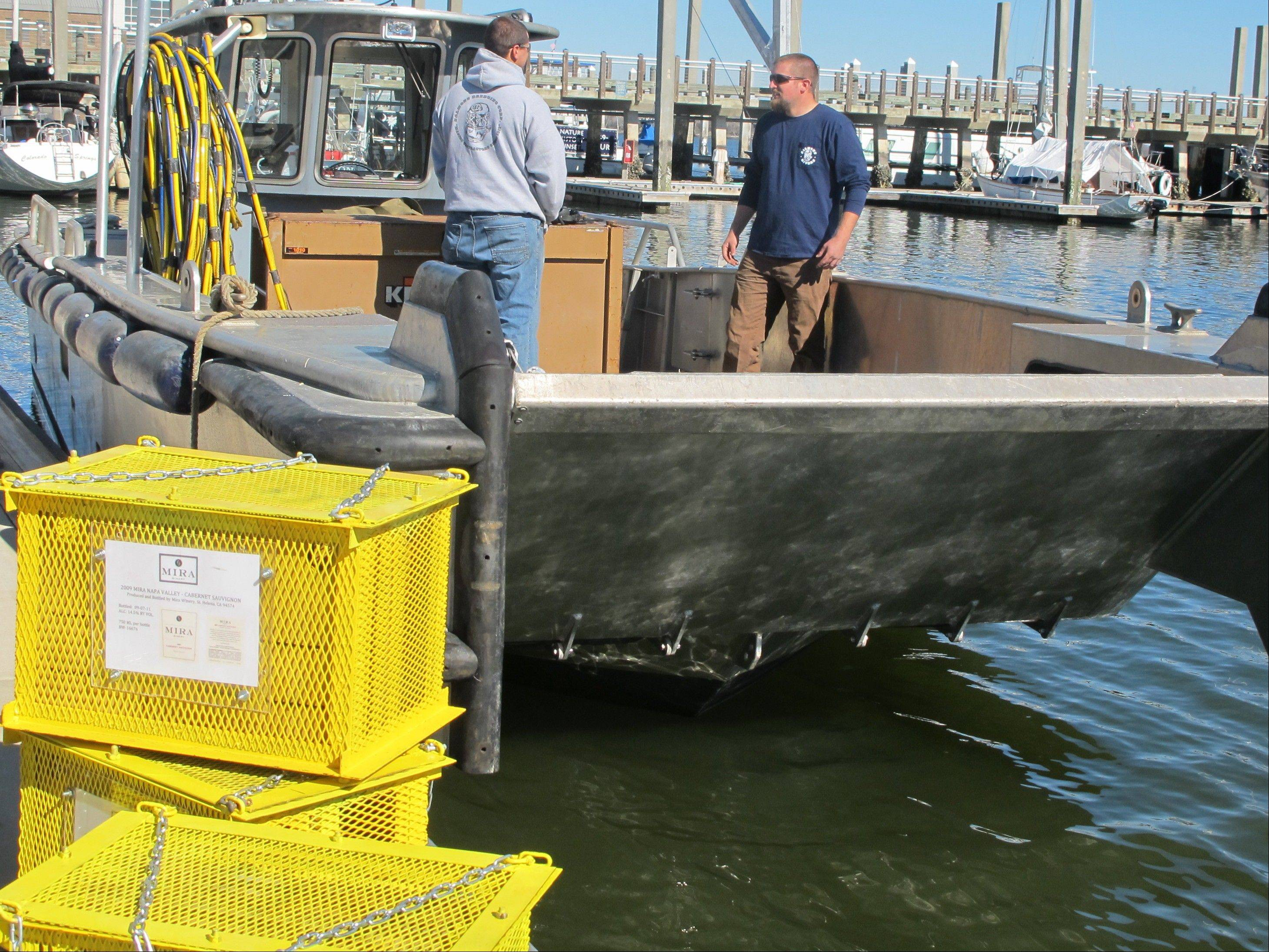 Bottles of cabernet sauvignon in protective steel cages, left, are ready to be loaded onto a boat in Charleston, S.C., Wednesday. Mira Winery of St. Helena, California, submerged four cases of wine in Charleston Harbor on Wednesday to see what effect the ocean has on aging the wine.
