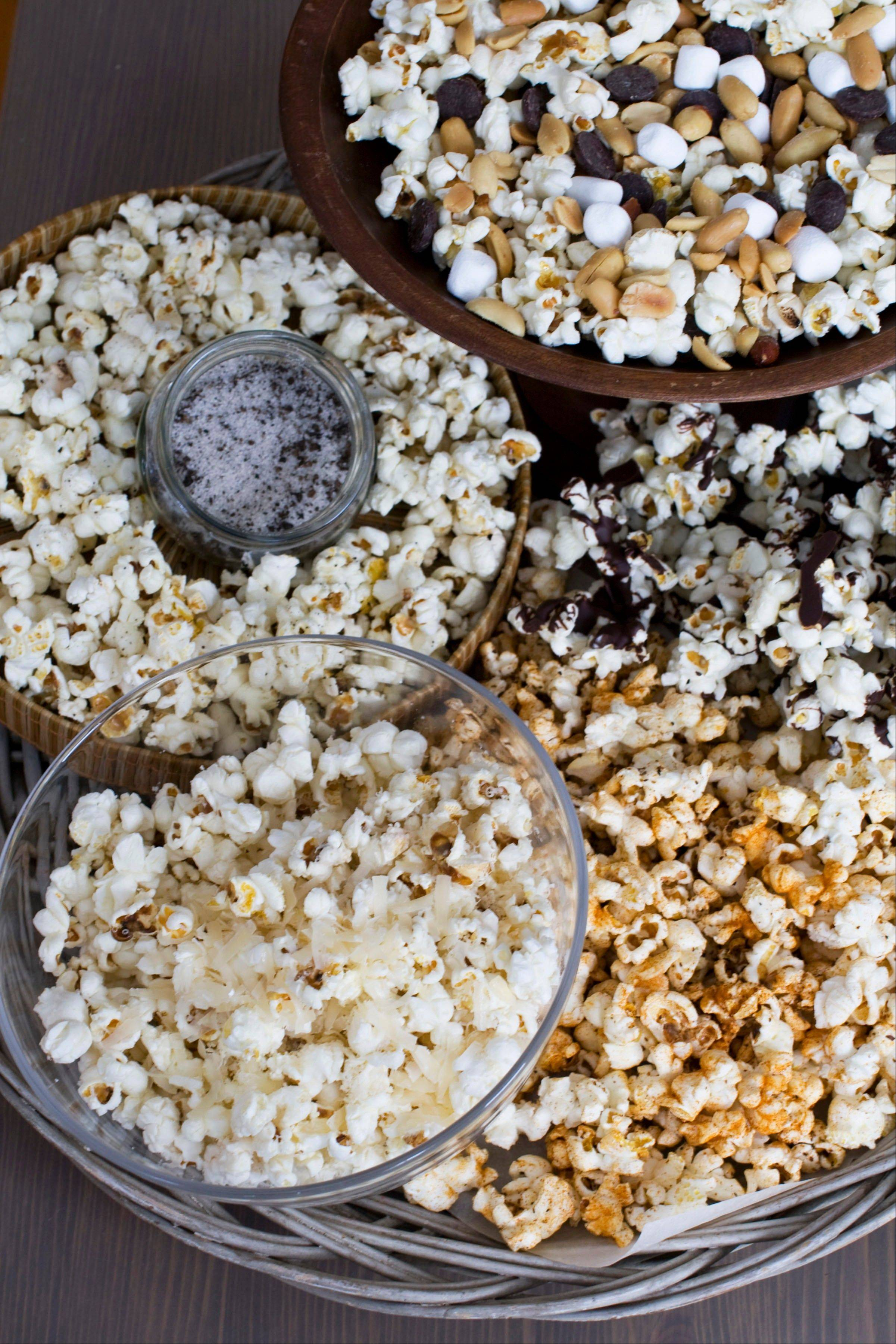 Stovetop Popcorn Many Ways, from top clockwise, mini marshmallows, chocolate chips and salted peanuts, melted chocolate, sweet and spicy barbeque rub, finely grated parmesan cheese, and truffle salt.