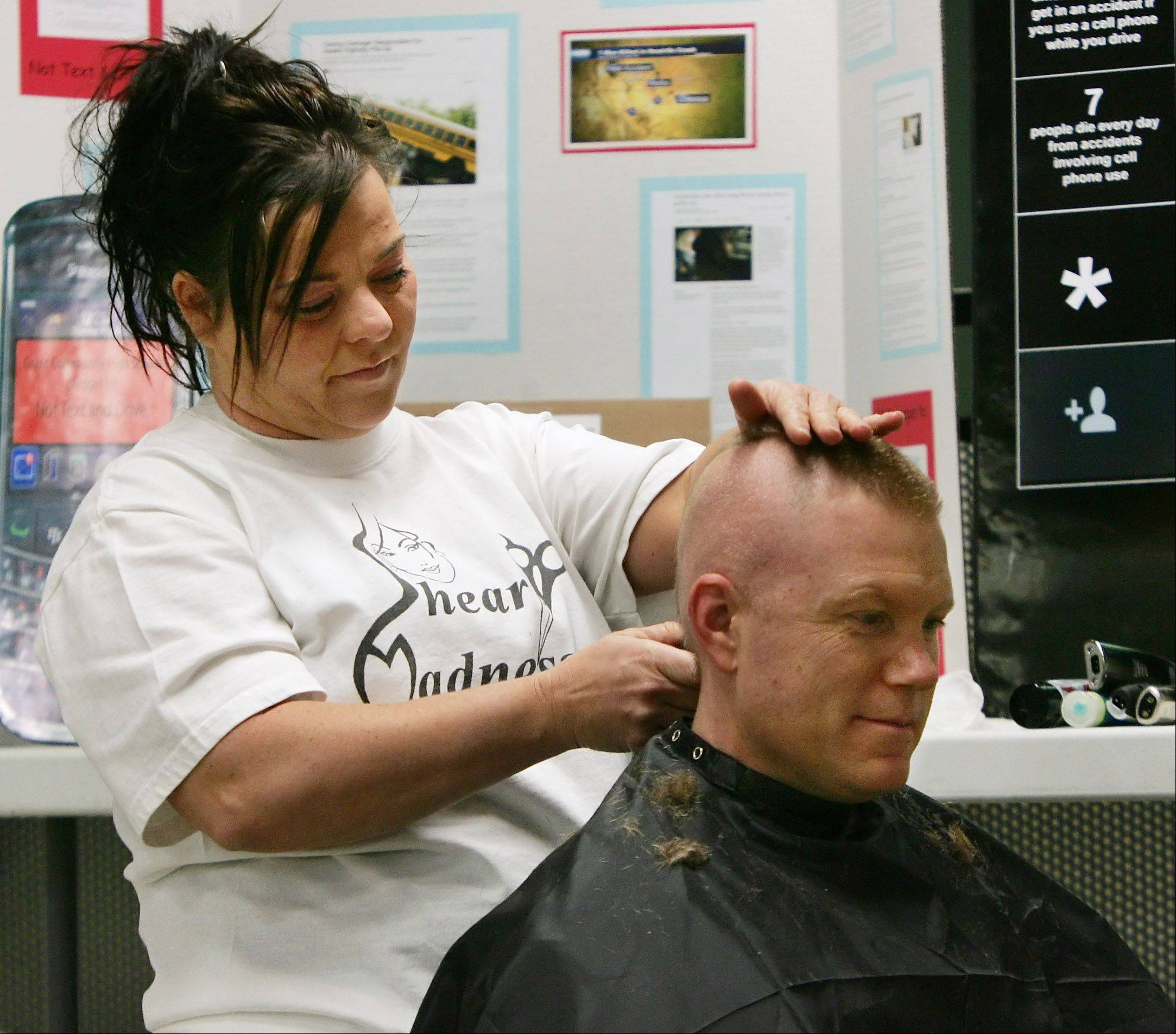 Fox Lake police officer Russell Zander, the resource officer at Grant High School, had his hair shaved into a mohawk style Wednesday after more than 850 students and staffers signed pledges promising not to text while driving.