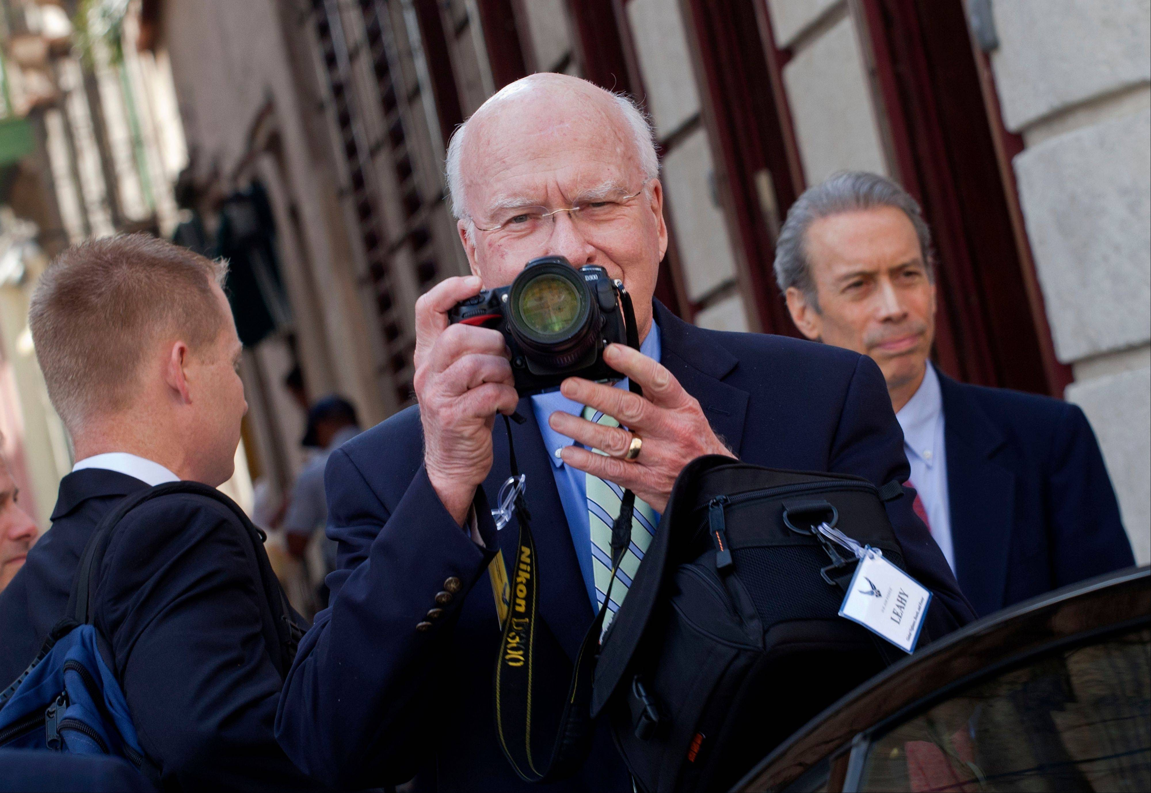 U.S. Sen. Patrick Leahy, center, takes pictures with his camera after a meeting with Cuba's Foreign Minister Bruno Rodriguez in Old Havana, Cuba, Tuesday, Feb. 19, 2013. U.S. lawmakers met Tuesday with Cuba's foreign minister and visited an American man whose detention and long sentence in Cuba has hampered efforts to improve ties between the countries.