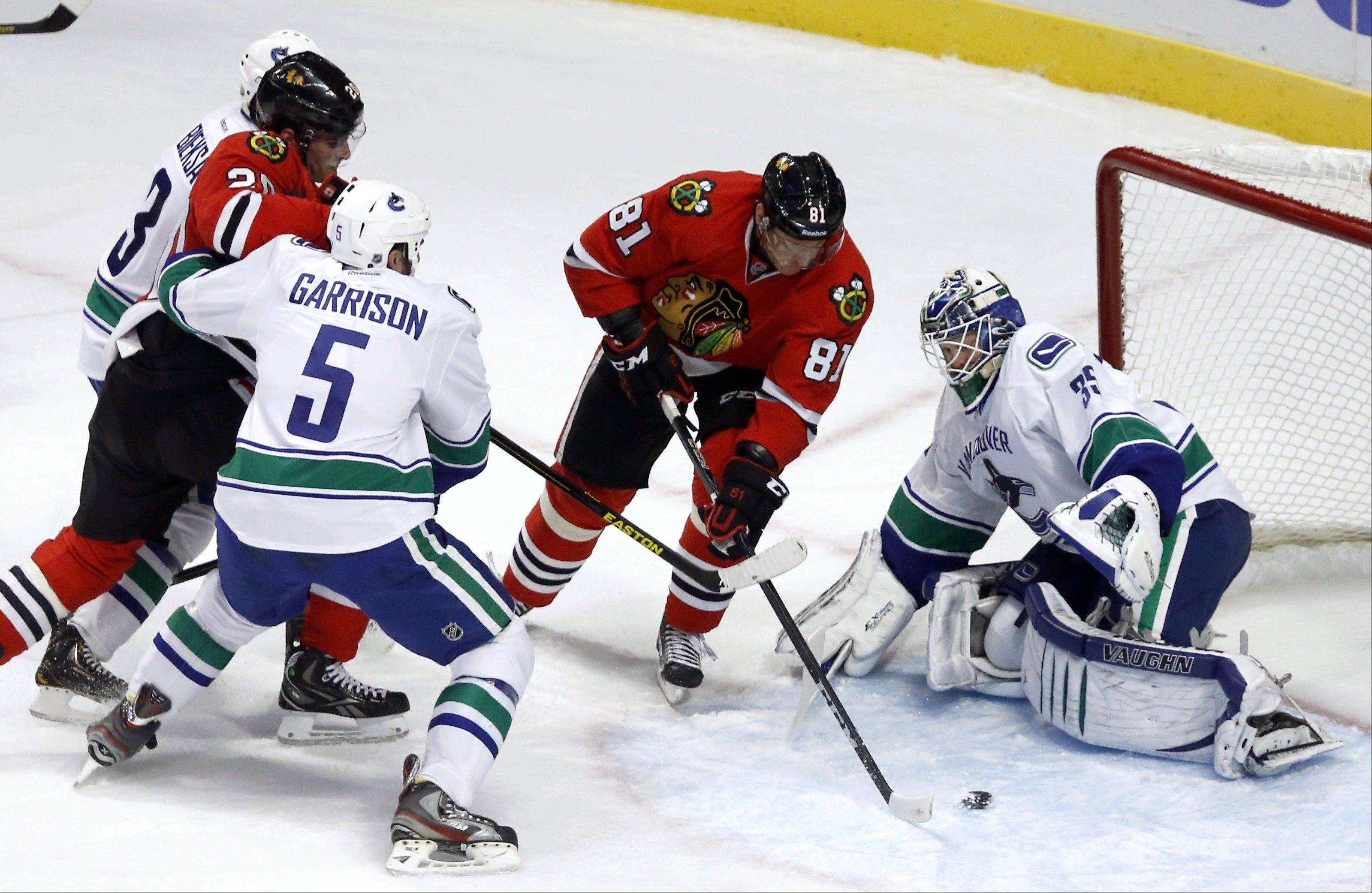Chicago Blackhawks right wing Marian Hossa splits the defense of Vancouver Canucks' Kevin Bieksa, Jason Garrison and goalie Cory Schneider to score his second goal in the second period .