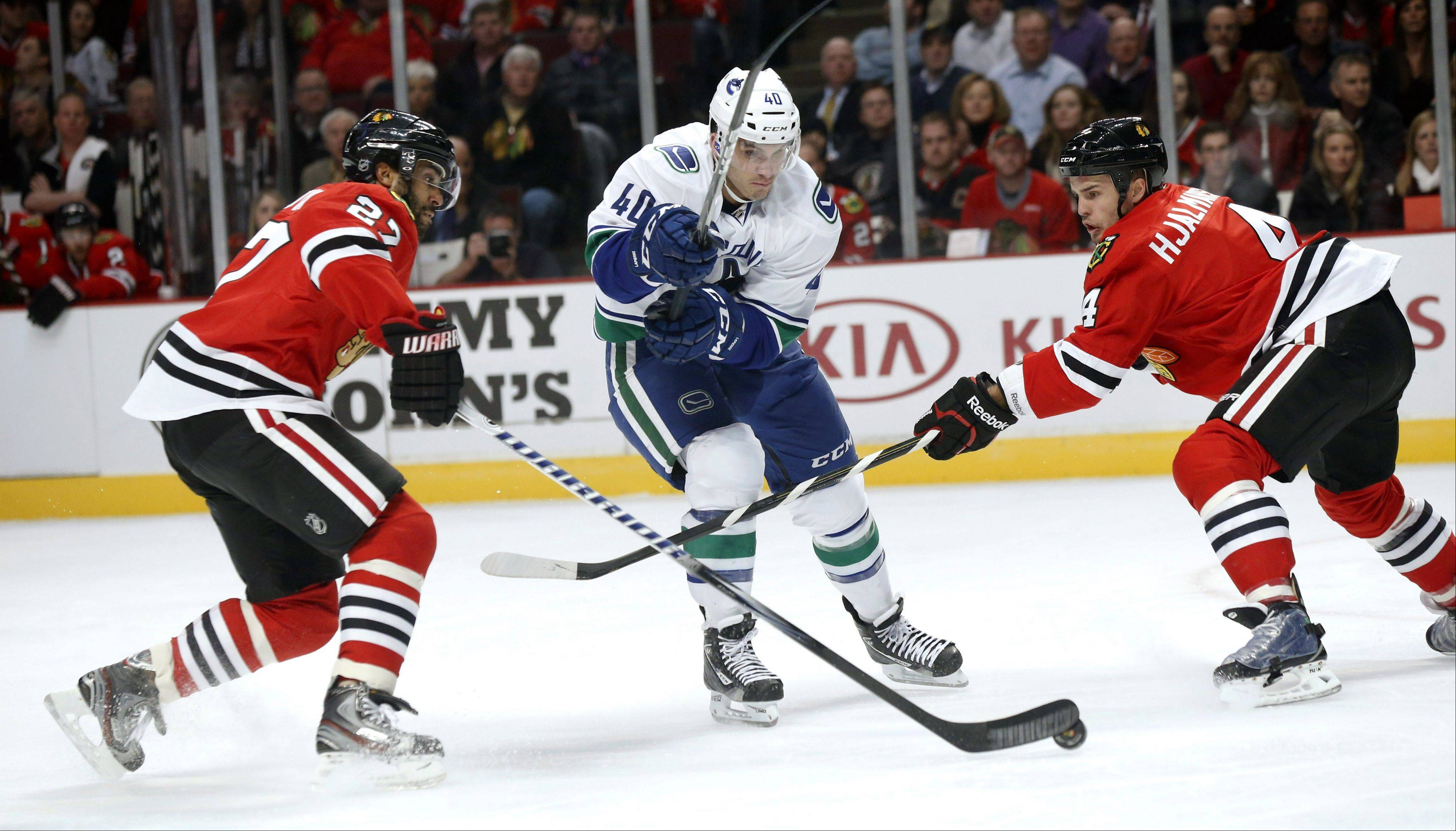 Vancouver Canucks center Maxim Lapierre tries to split the defense of Chicago Blackhawks' Johnny Oduya and Niklas Hjalmarsson during the first period.