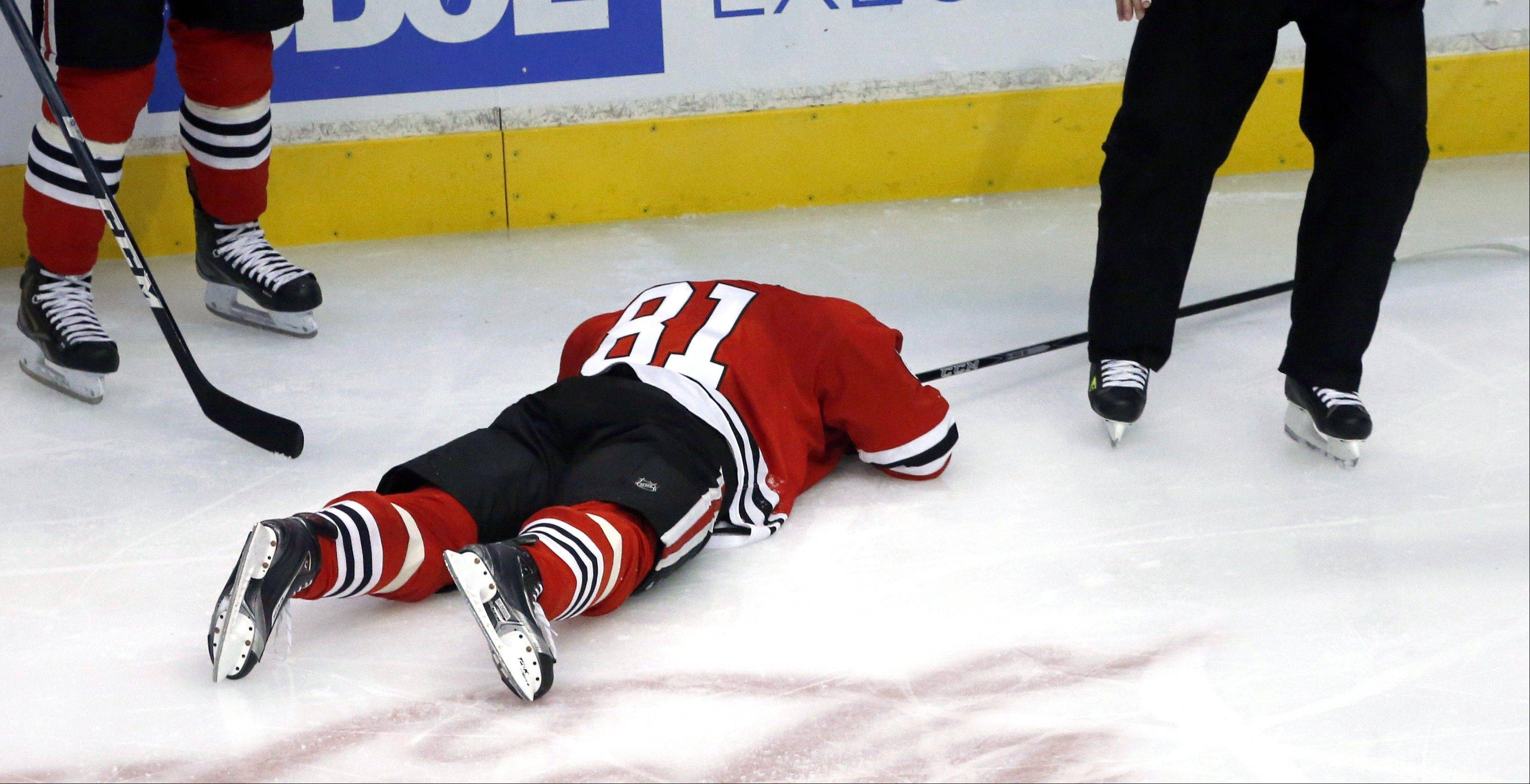 Chicago Blackhawks right wing Marian Hossa lays on the ice after being hit in the back of the head by Vancouver Canucks right wing Jannik Hansen.